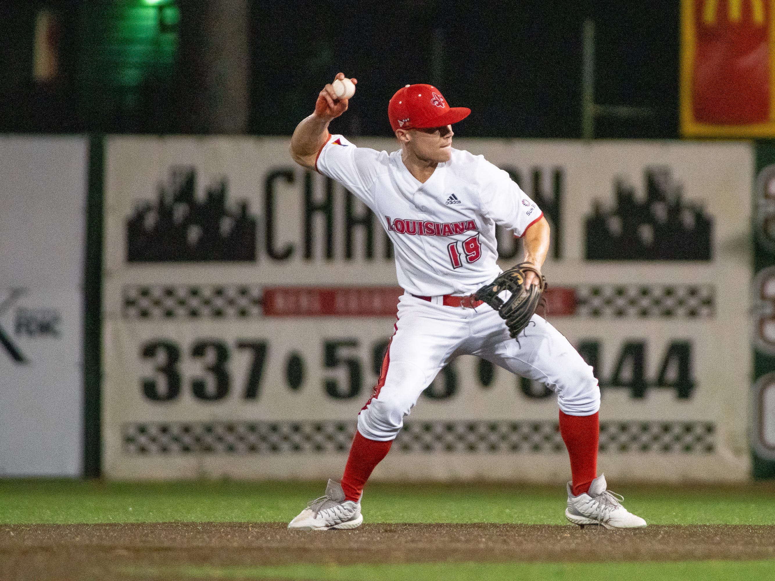 """UL's Hunter Kasuls throws the ball to first base as the Ragin' Cajuns take on the Southern Miss Golden Eagles at M.L. """"Tigue"""" Moore Field on Wednesday, March 13, 2019."""