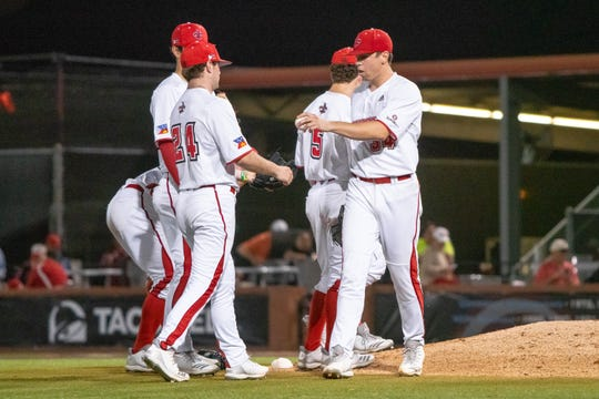 UL's Grant Cox (right) hands off the ball to reliever Caleb Armstrong as the Ragin' Cajuns used six pitchers in 6-5, 12-innings win over Southern Mississippi on Wednesday night at The Tigue.