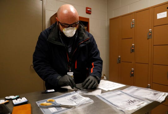 Dennis Lowe, commander of the Fairfield Athens Major Crimes Unit, takes a sample of a white powder from an evidence bag in the property room March 4, 2019, at the Fairfield County Sheriff's Office in Lancaster. Lowe was demonstrating a safer field test system to FCSO Chief Deputy Alex Lape. MCU detectives have been using the test which is sensitive enough to detect small amounts of substances from the outside of a bag which would limit the tester's exposure to potentially dangerous drugs like fentanyl and carfentanil.