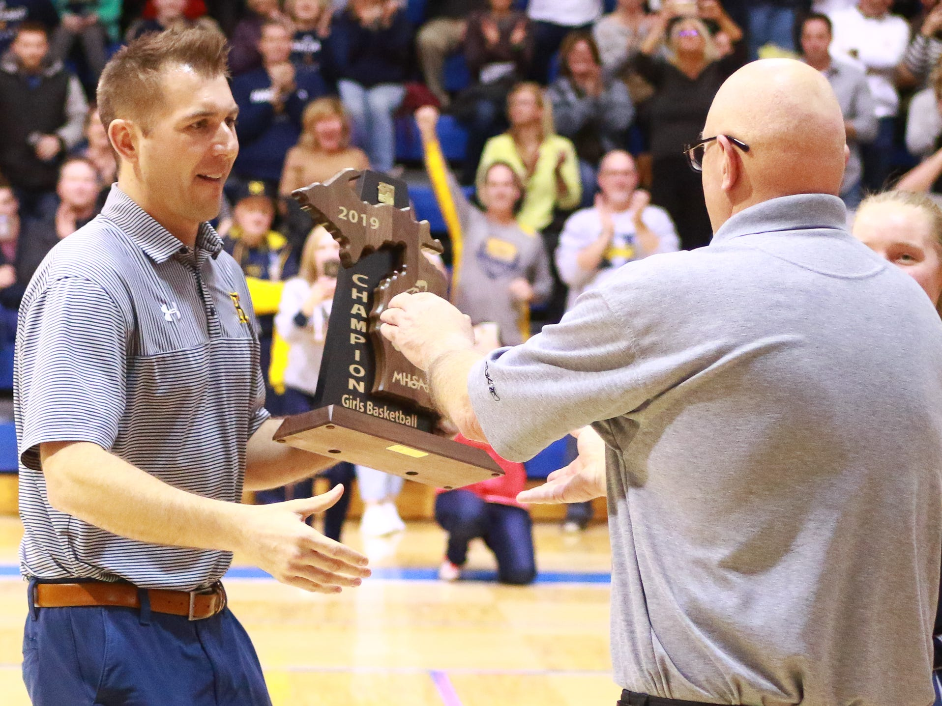 Hartland coach Don Palmer (right) accepts the regional championship trophy from Hartland athletic director JD Wheeler following a 50-46 victory over Walled Lake Western at Lakeland on Wednesday, March 13, 2019.
