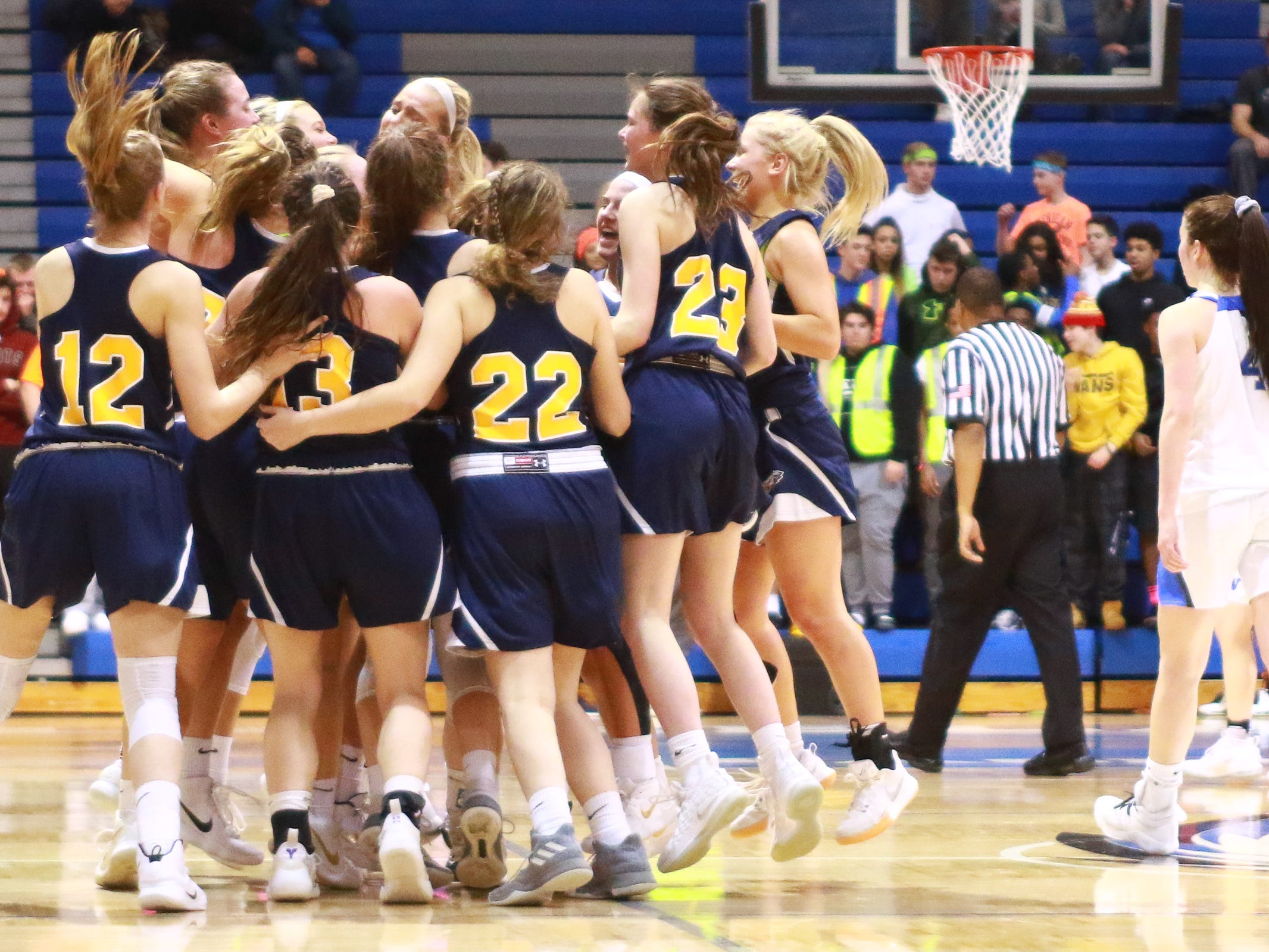Hartland basketball players celebrate a 50-46 victory over Walled Lake Western in the Division 1 regional championship game at Lakeland on Wednesday, March 13, 2019.