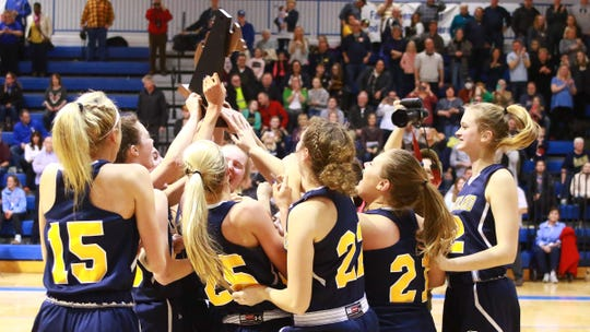 Hartland basketball players celebrate with the regional championship trophy after a 50-46 victory over Walled Lake Western at Lakeland on Wednesday, March 13, 2019.