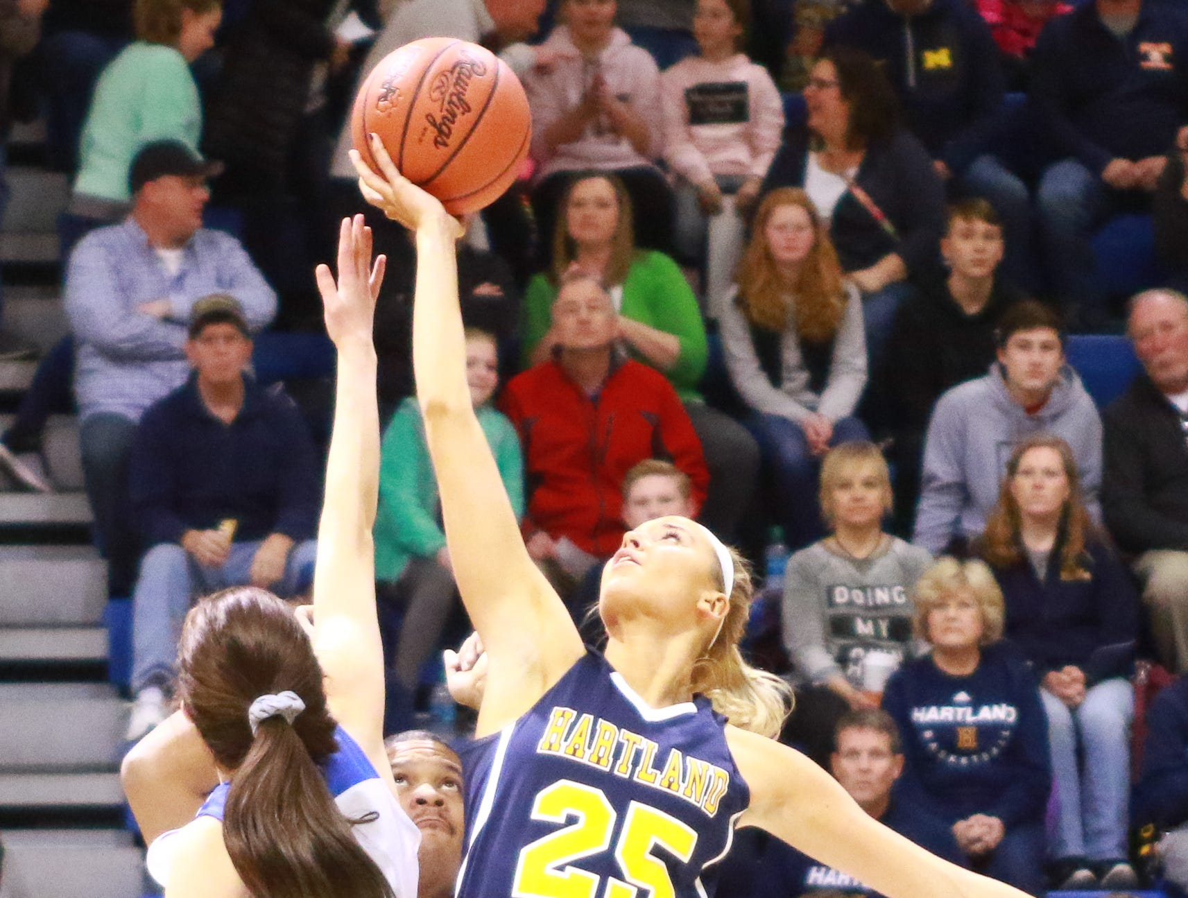 Hartland's Whitney Sollom (25) controls the opening tip in a 50-46 victory over Walled Lake Western in a regional championship basketball game at Lakeland on Wednesday, March 13, 2019.