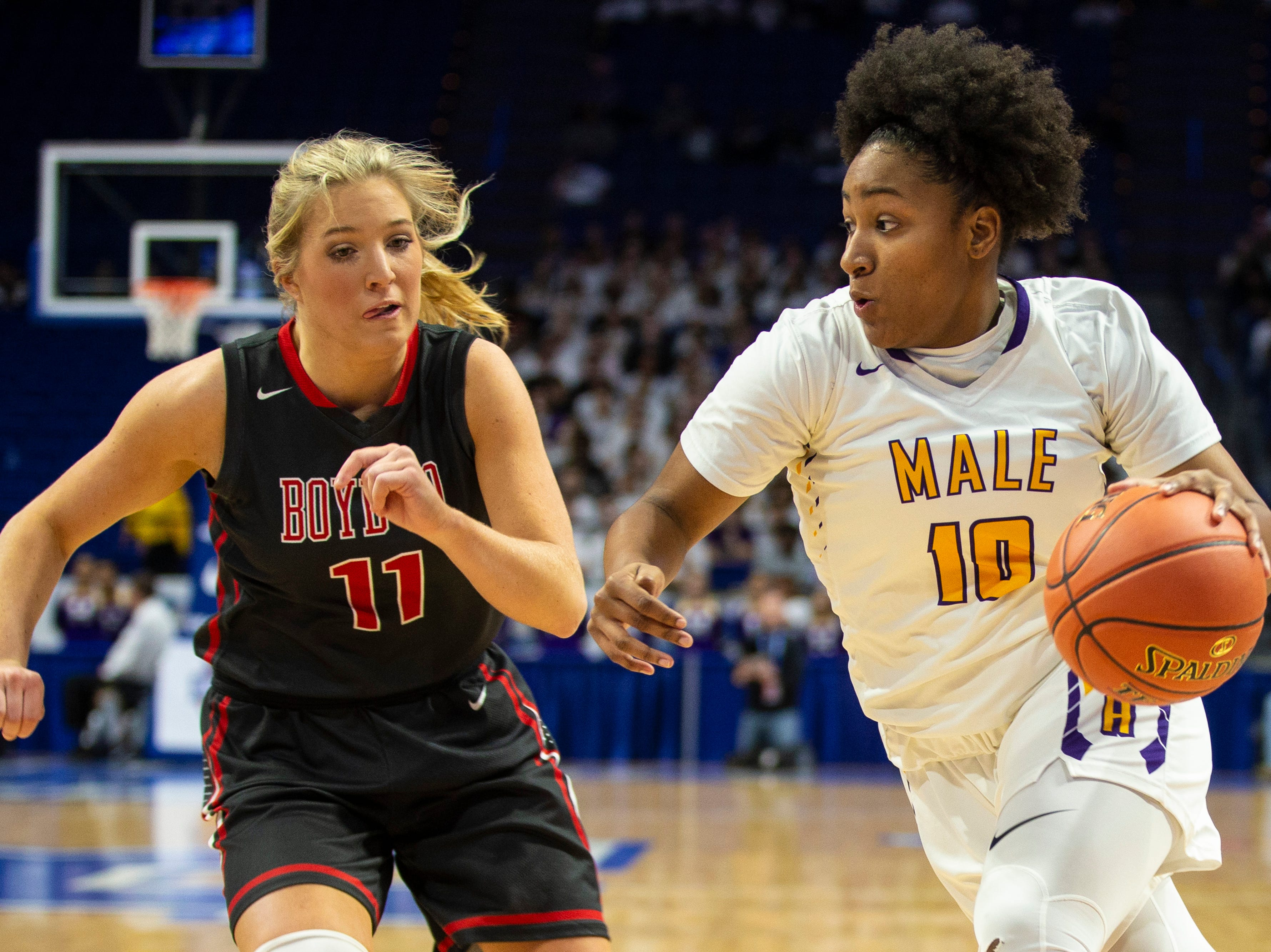 Boyd County's Graci Borders, left, looks to defend Male's Destiny Combs as Boyd County took on Louisville Male in the KHSAA state basketball tournament in Rupp Arena. Male eliminated Boyd County 74-56. March 14, 2019