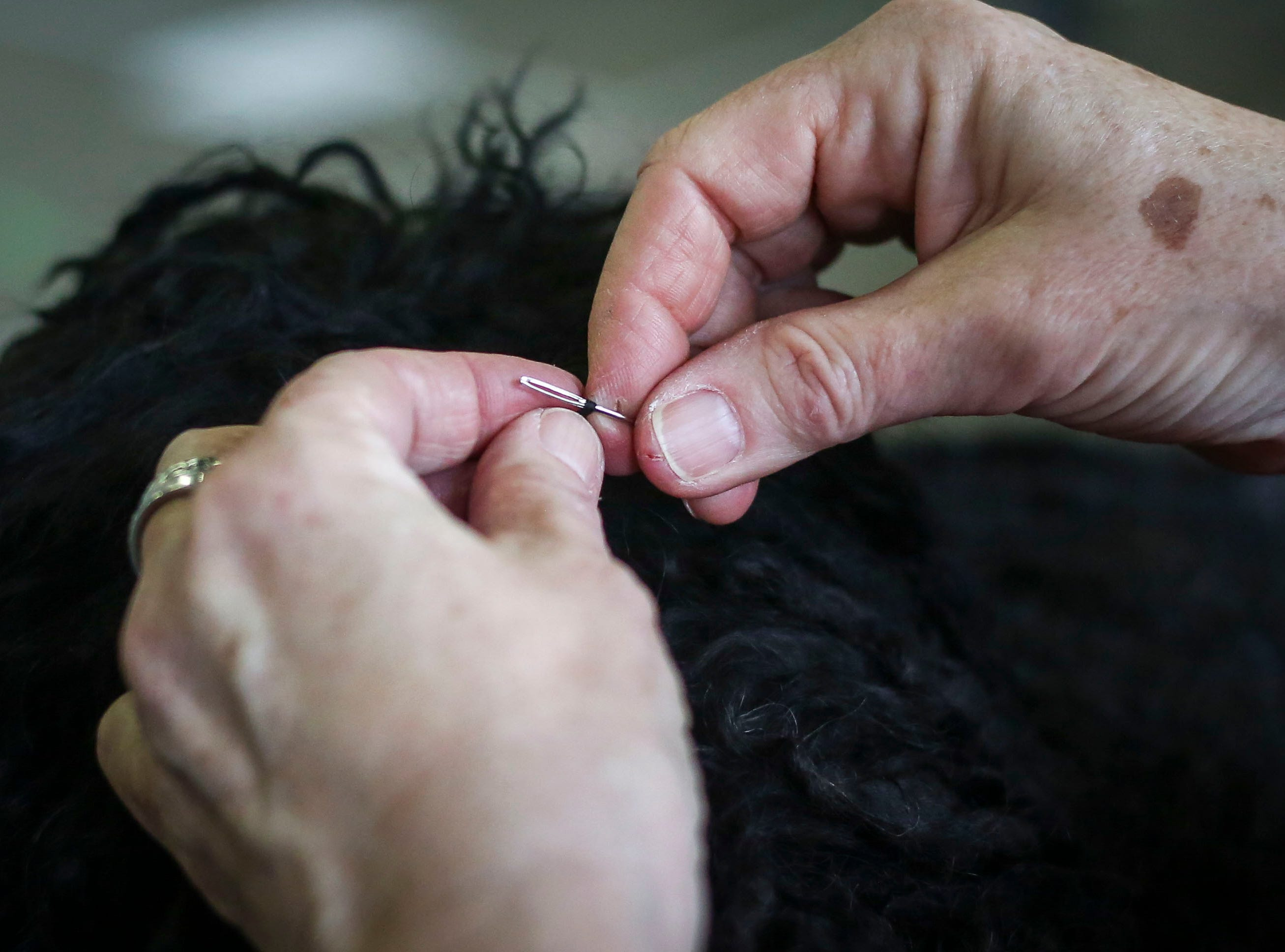 Juli Schuh fixes Parker's dreaklocks. Parker is a 6-year-old puli competing in the Kentuckiana Cluster of Dog Shows at the Kentucky Fair and Exposition Center in Louisville, Ky. on Thursday, March 14, 2019.