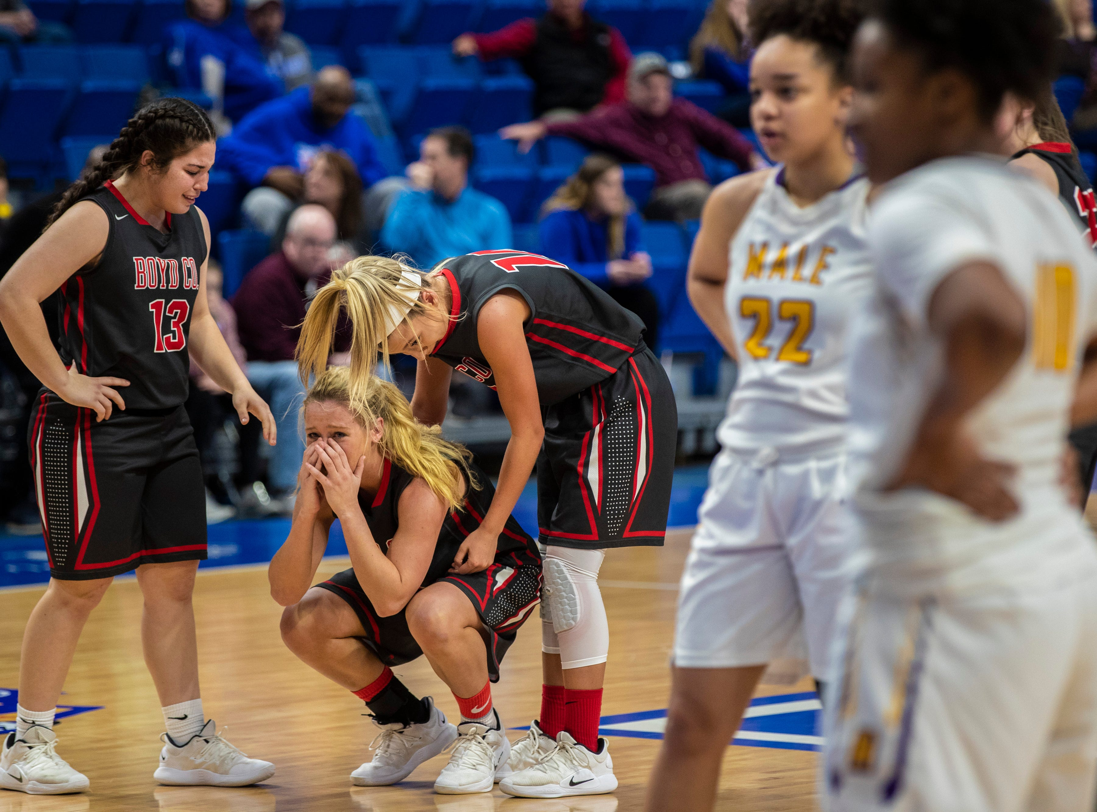 Boyd County's Graci Opell, from left, looks on as teammate Savannah Wheeler is comforted by Harley Painter as they react to their imminent defeat to Louisville Male in the KHSAA state basketball tournament in Rupp Arena. Male eliminated Boyd County 74-56. March 14, 2019