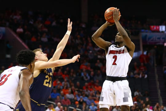Louisville Cardinals guard Darius Perry (2) shoots the ball against Notre Dame Fighting Irish guard Dane Goodwin (23) in the first half in the ACC conference tournament at Spectrum Center in Charlotte, North Carolina, on Wednesday, March 13, 2019.
