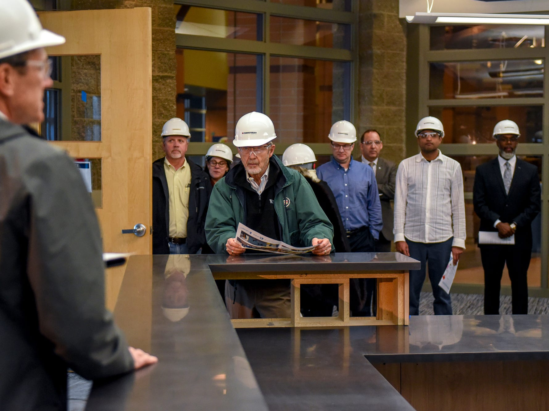 Former Lansing mayor David Hollister, center, listens in the main office during a tour of the construction of the new Eastern High School on Thursday, March 14, 2019, in Lansing. The project is being funded by the district's successful Pathway Promise millage, which was passed by voters in 2016. The building was formerly Pattengill Academy.