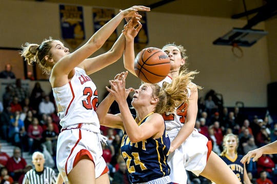 Dewitt's Annie McIntosh, center, and Coldwater's Taylor Lindsay, left, and Lauren Anderson go for a rebound during the second quarter on Wednesday, March 13, 2019, at Caledonia High School.