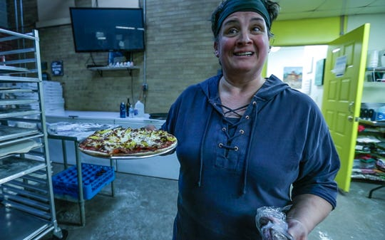 Marilyn Frank holds a dish of pizza ready to serve her customers Thursday, Feb. 21, 2019, at Marilyn's Fire Station & Catering in Medford