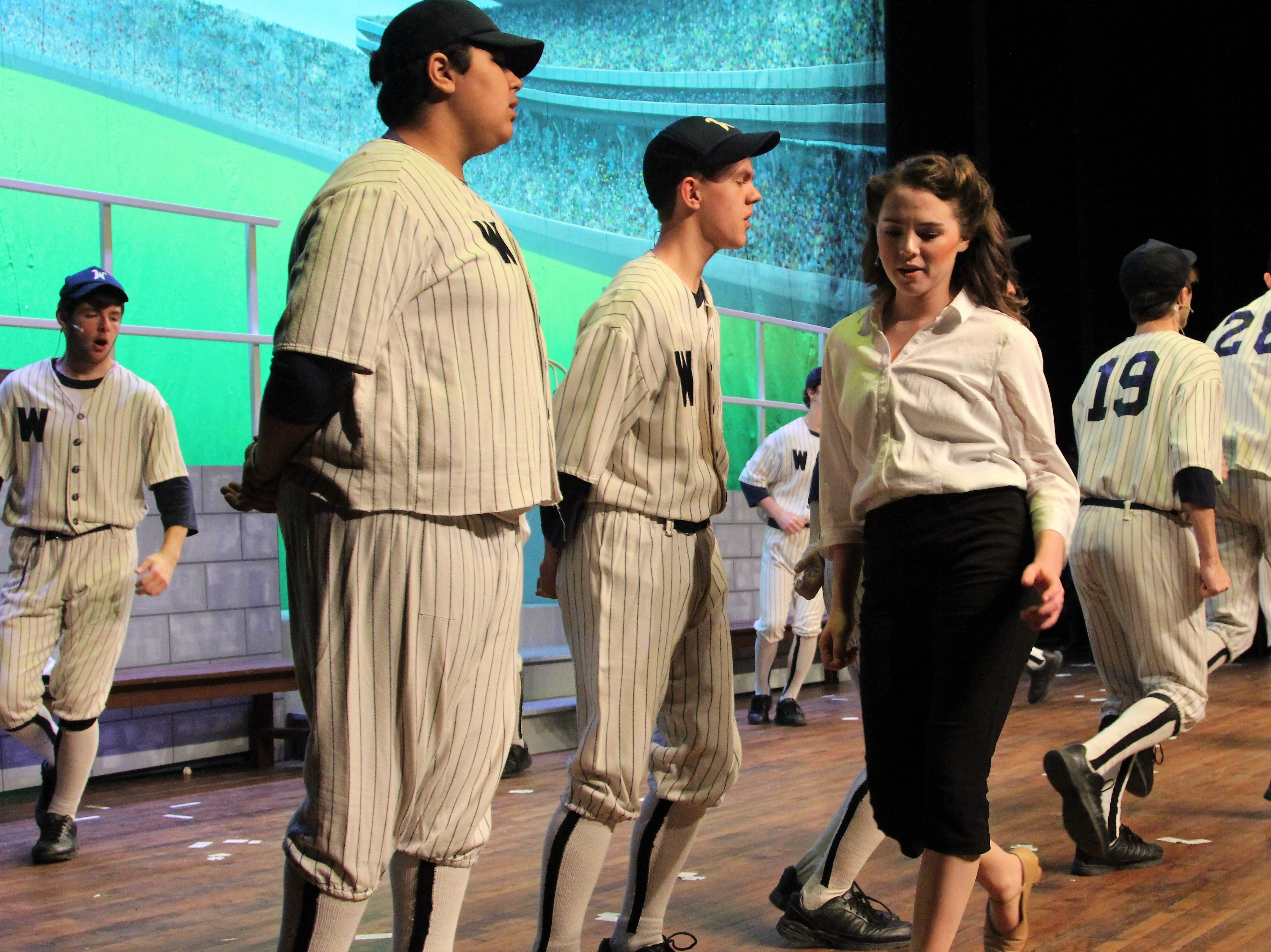 """Pleasant senior Alyson Hoffman, who plays probing reporter Gloria Thorpe,  walks by a group of baseball players with the Washington Senators during a rehearsal for her high school's production of """"Damn Yankees."""""""