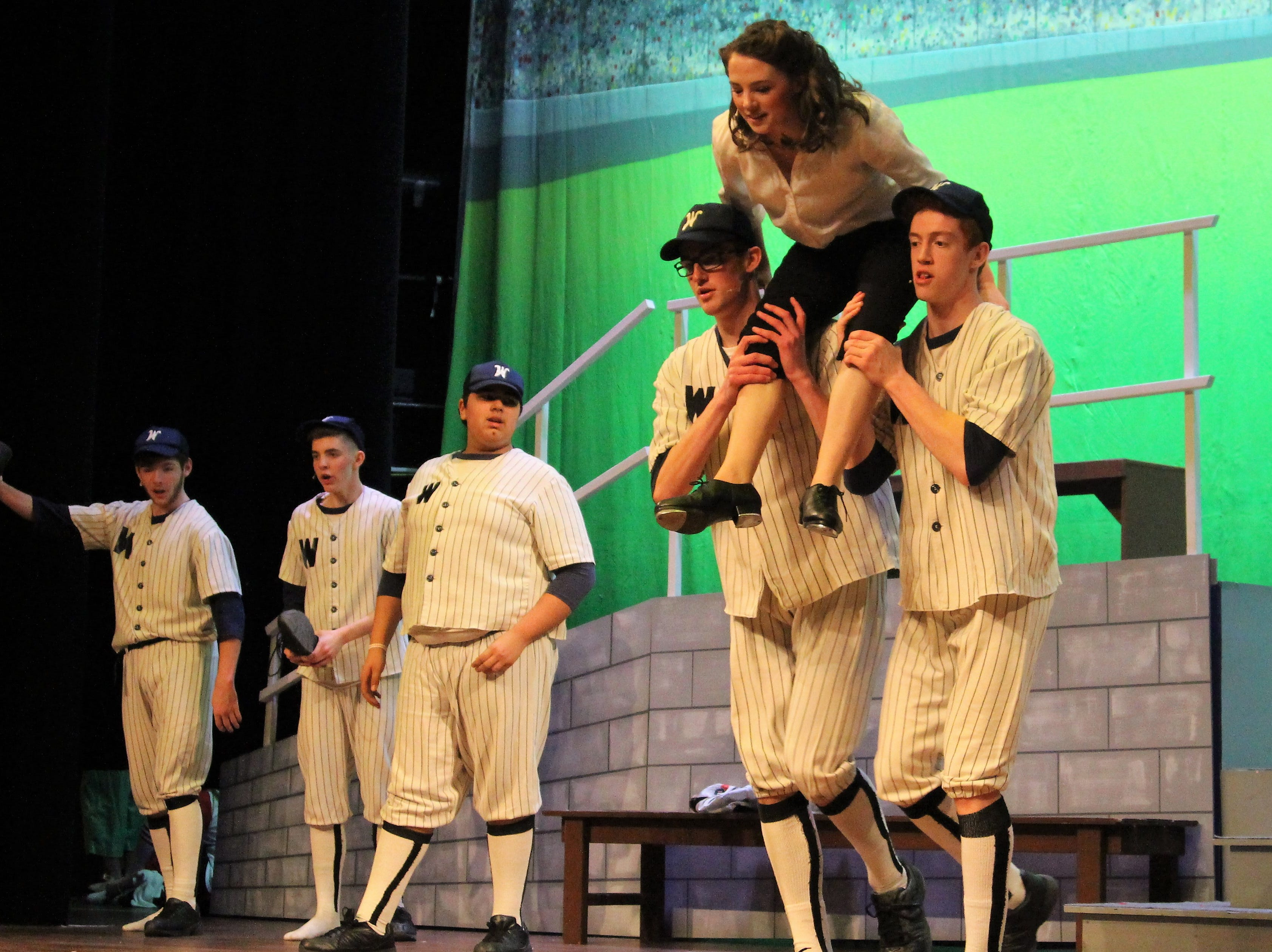 """Pleasant senior Alyson Hoffman glides through the air on Wednesday as probing reporter Gloria Thorpe during a dress rehearsal for her high school's production of """"Damn Yankees."""""""