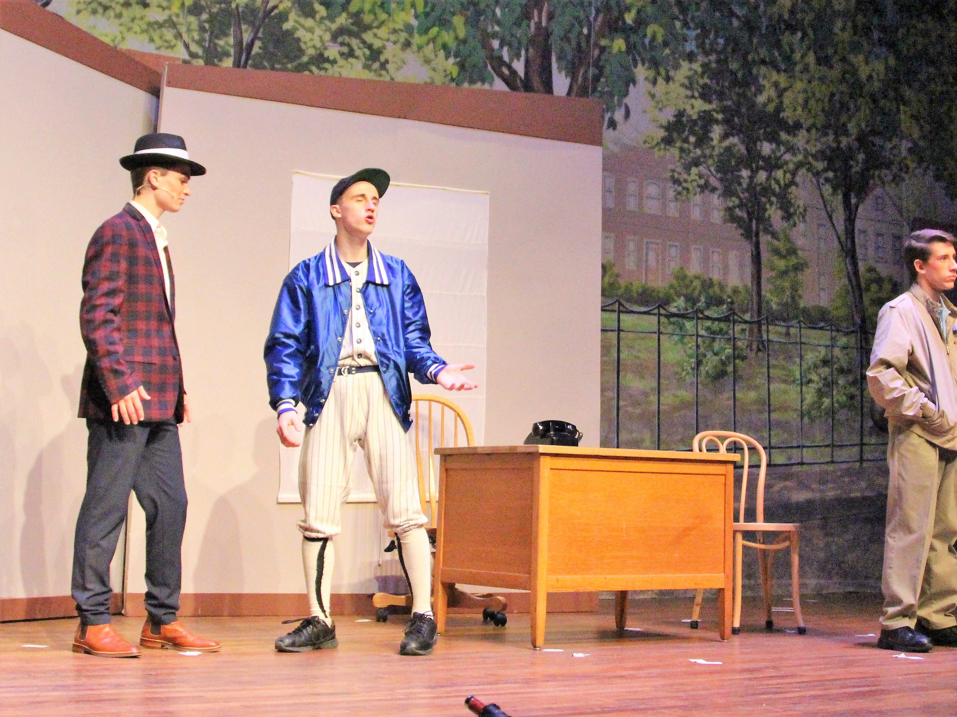 """Ryan Roth (center) walks on stage during a Wednesday dress rehearsal of """"Damn Yankees"""" as hardworking baseball manager Van Buren. The show is slated for this weekend at the Marion Palace Theatre."""