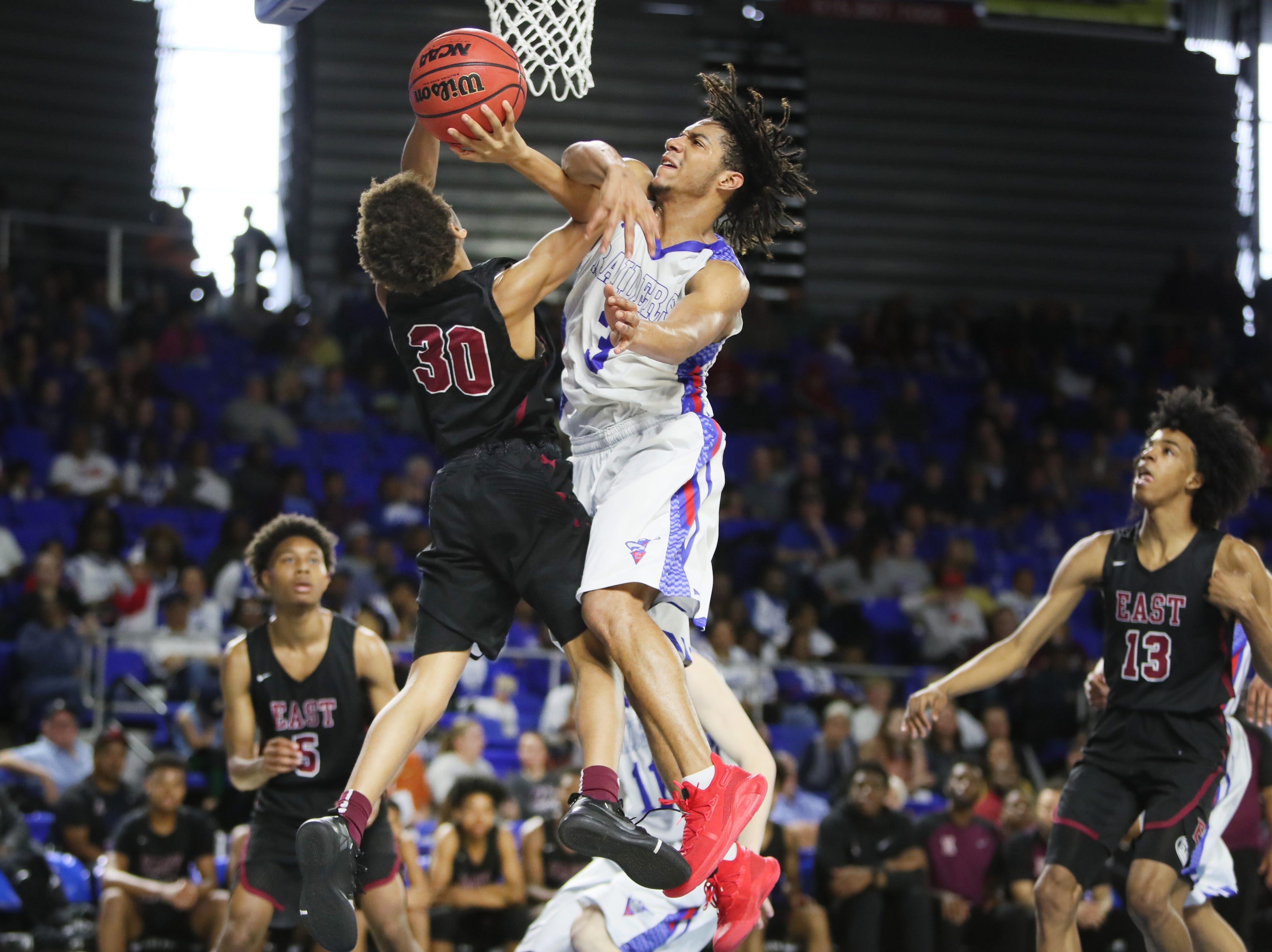 Memphis East's Terrence Jacobs draws a foul from Cleveland's Isaiah Johnson during the TSSAA Division I basketball state tournament at the Murphy Center in Murfreesboro, Tenn. on Thursday, March 14, 2019.