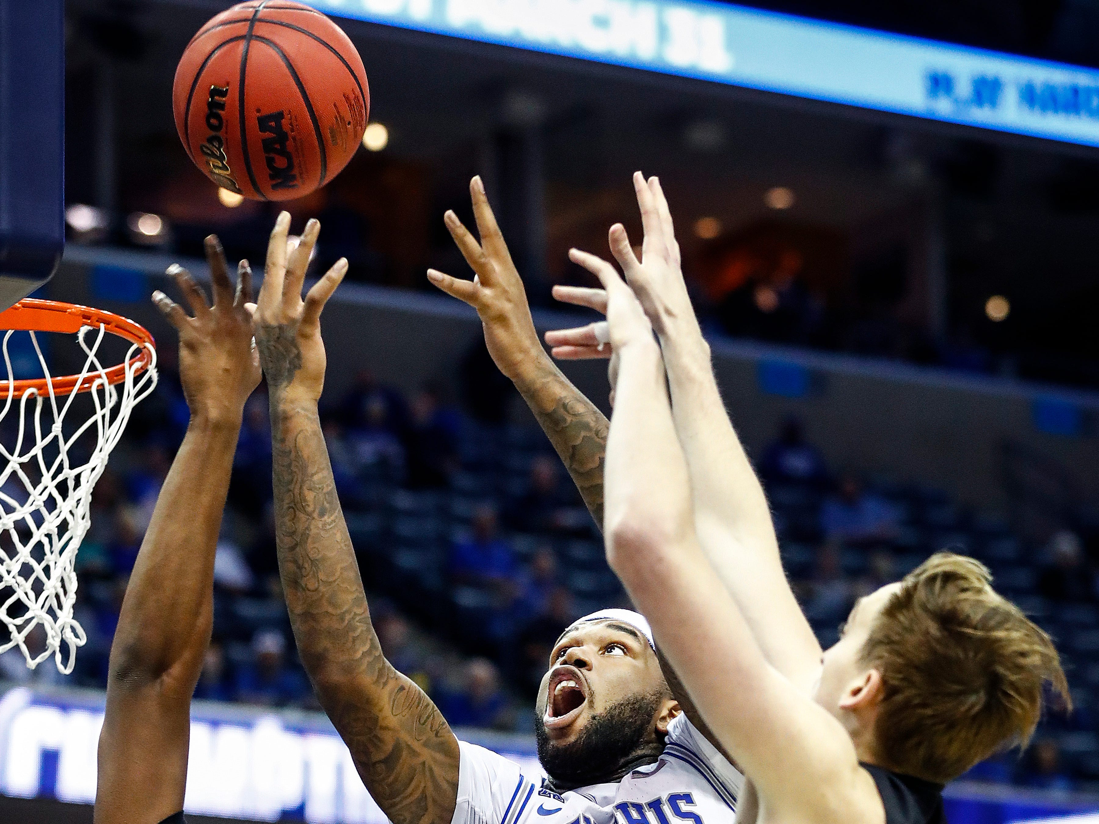 Memphis forward Mike Parks Jr. (middle) tries to grab a rebound away from Tulane defenders Blake Paul (left) and Moses Wood (right) during action of their first round AAC Tournament game at the  FedExForum, Thursday, March 14, 2019.