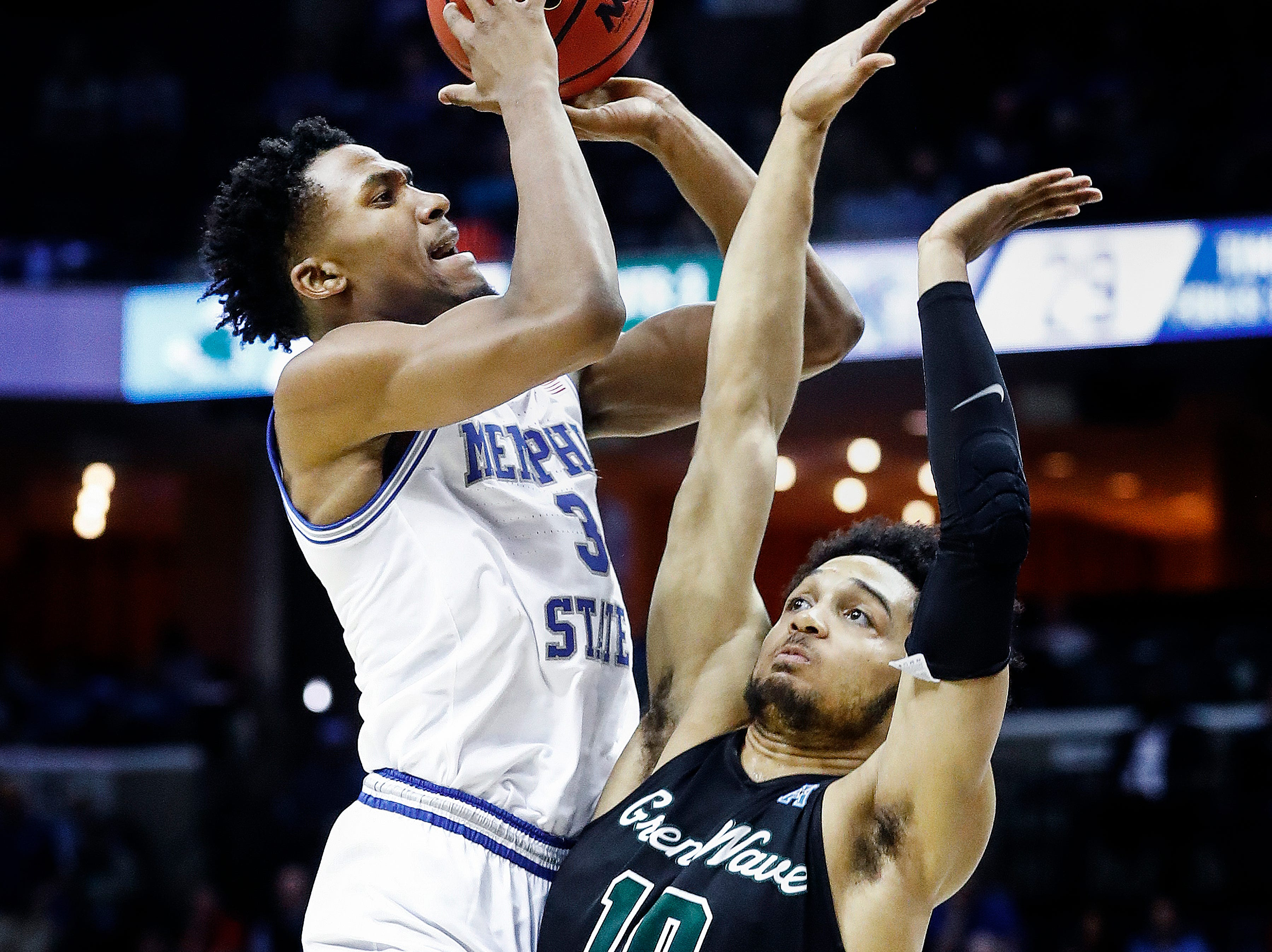 Memphis guard Jeremiah Martin (left) is fouled by  Tulane defender Caleb Daniels (right) during action of their first round AAC Tournament game at the  FedExForum, Thursday, March 14, 2019.