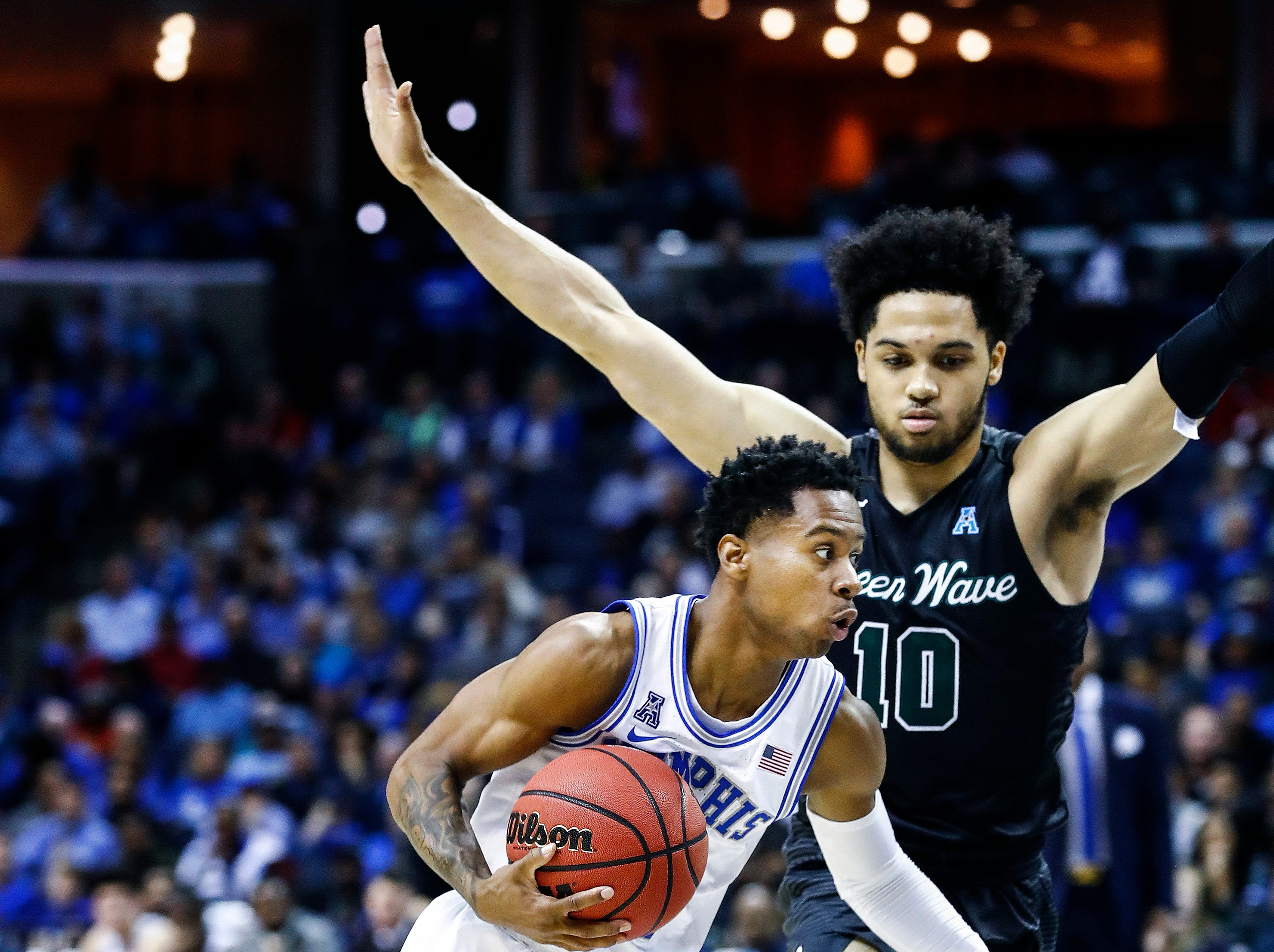 Memphis guard Tyler Harris (left) drives the lane against Tulane defender Caleb Daniels (right) during action of their first round AAC Tournament game at the  FedExForum, Thursday, March 14, 2019.