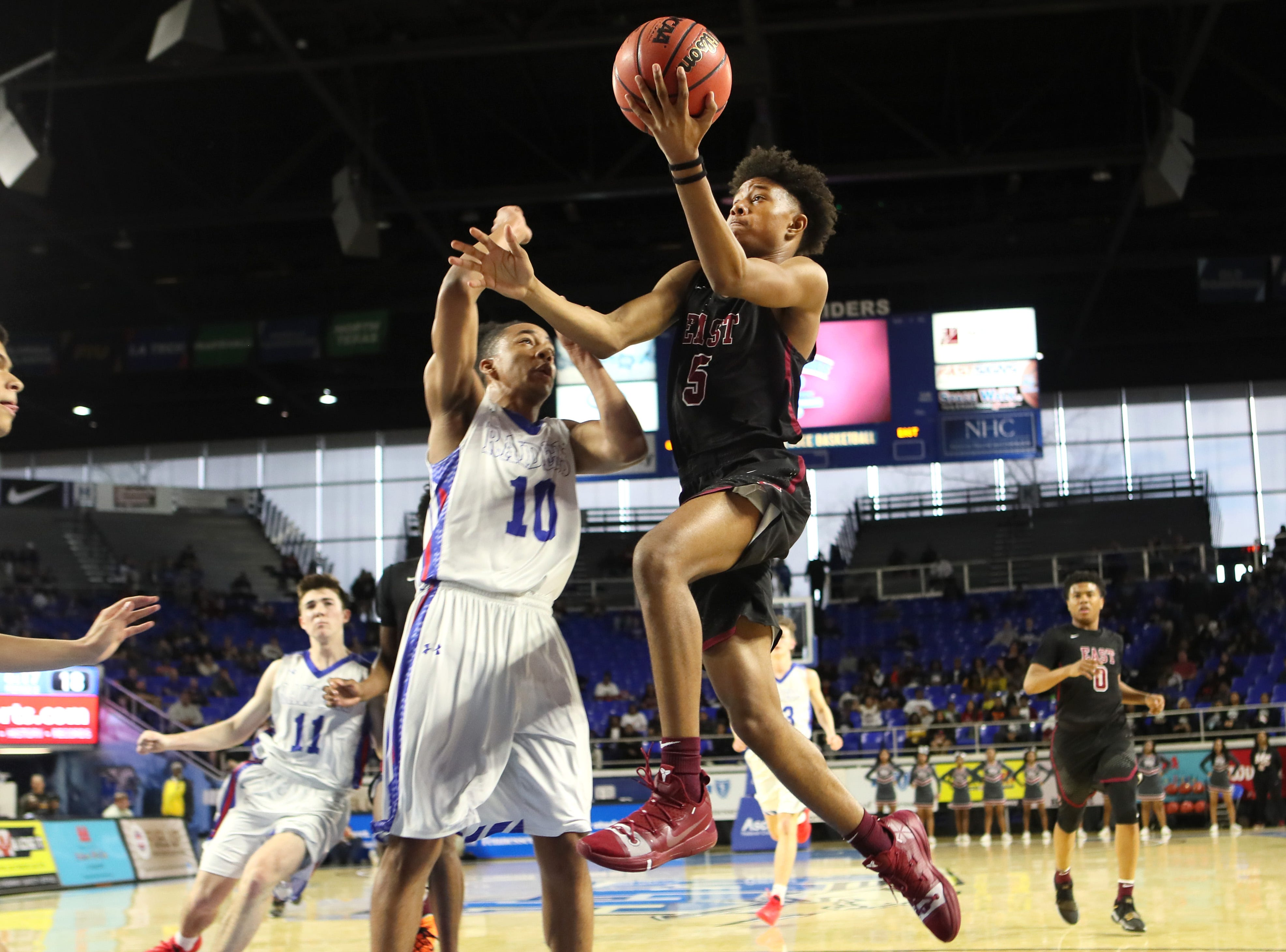 Memphis East's Tadarius Jacobs tries to lay the ball up past Cleveland's Jacobi Wood during the TSSAA Division I basketball state tournament at the Murphy Center in Murfreesboro, Tenn. on Thursday, March 14, 2019.