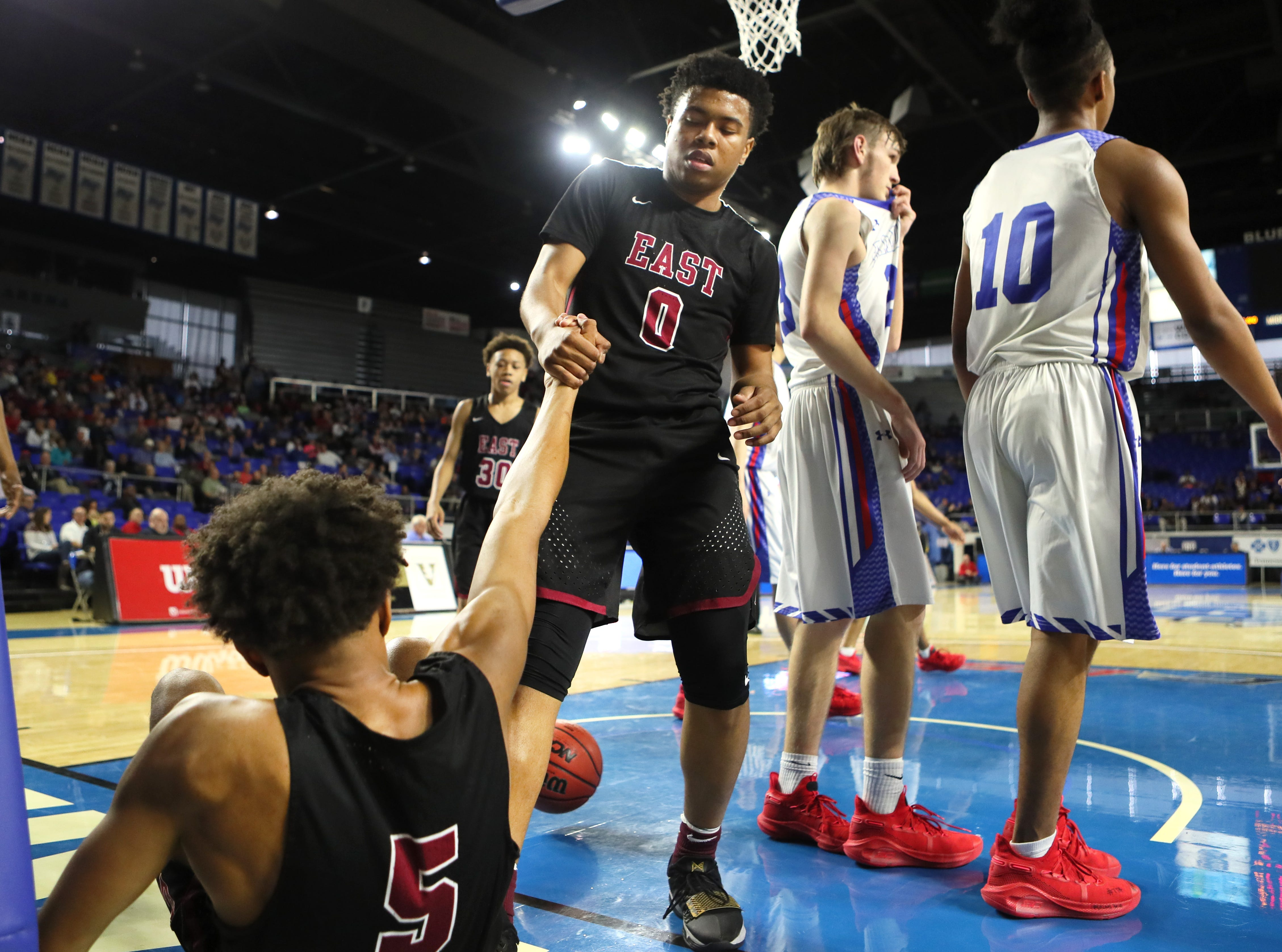 Memphis East's Derrein Merriweather helps up teammate Tadarius Jacobs as they take on Cleveland during the TSSAA Division I basketball state tournament at the Murphy Center in Murfreesboro, Tenn. on Thursday, March 14, 2019.