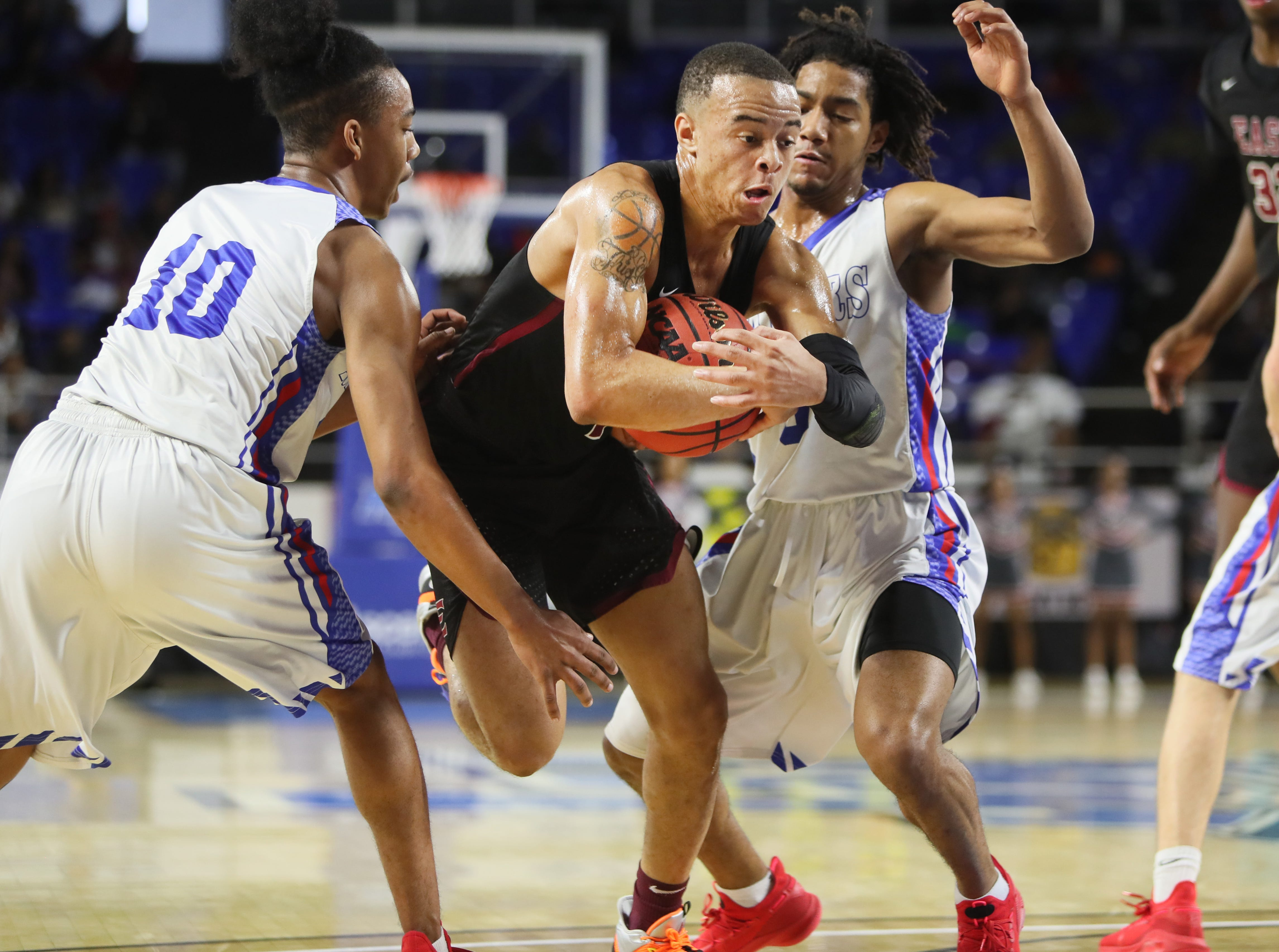 Memphis East's Antonio Thomas drives in between Cleveland's Jacobi Wood, left, and Isaiah Johnson during the TSSAA Division I basketball state tournament at the Murphy Center in Murfreesboro, Tenn. on Thursday, March 14, 2019.