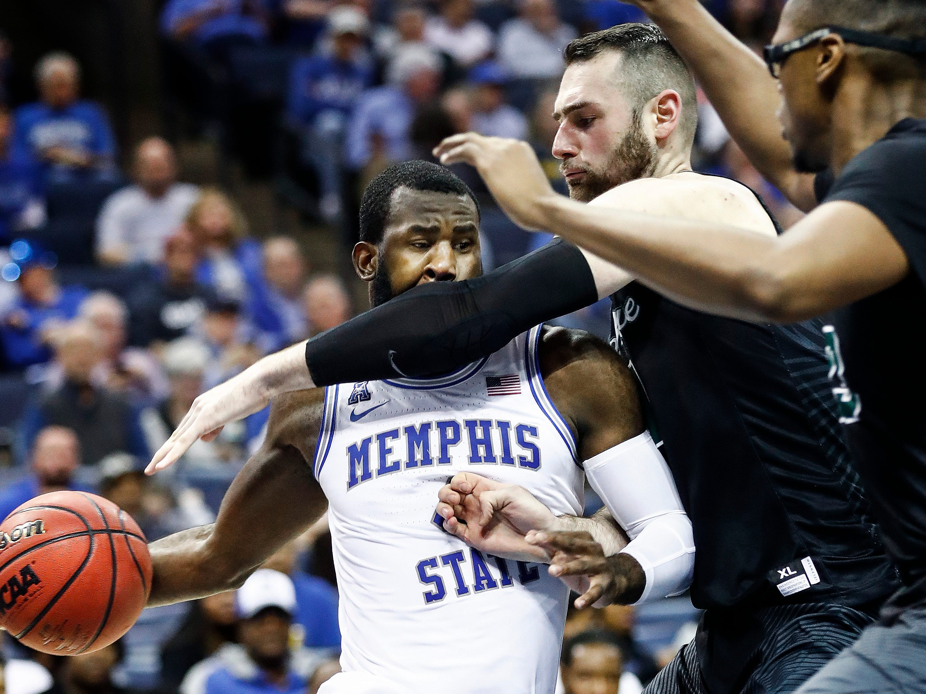 Memphis forward Raynere Thornton (left) loses the ball after running into Tulane defender Samir Sehic (right) during action of their first round AAC Tournament game at the  FedExForum, Thursday, March 14, 2019.