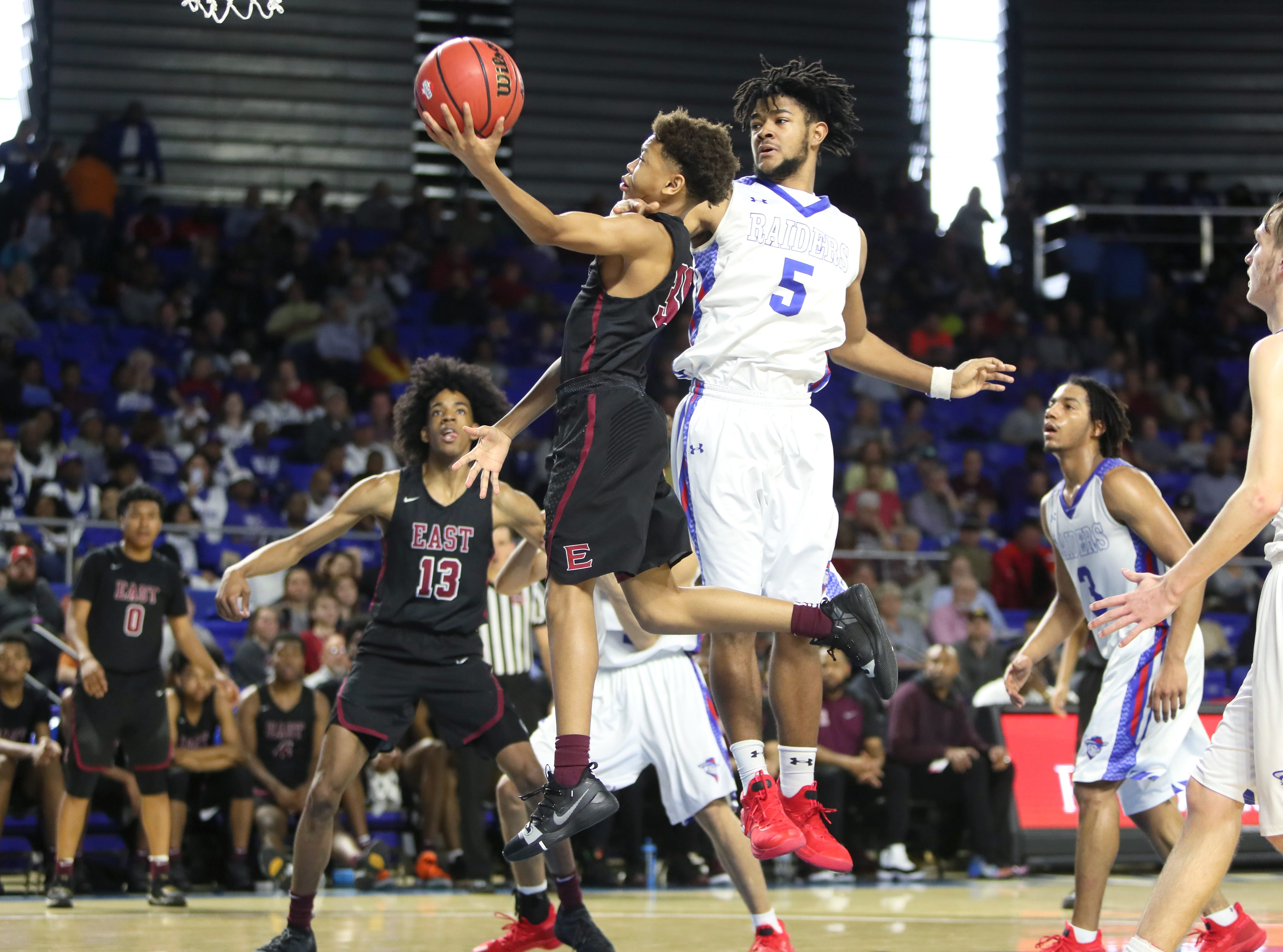 Memphis East's Terrence Jacobs lays the ball up past Cleveland's Darius Howard during the TSSAA Division I basketball state tournament at the Murphy Center in Murfreesboro, Tenn. on Thursday, March 14, 2019.