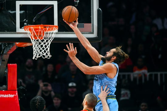 Memphis Grizzlies center Joakim Noah (55) shoots a layup as he is fouled by Atlanta Hawks center Alex Len during the first quarter of an NBA basketball game, Wednesday, March 13, 2019, in Atlanta. (AP Photo/John Amis)