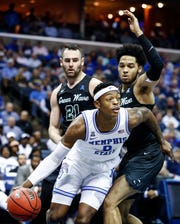 Memphis forward Kyvon Davenport (middle) drives the lane against Tulane defenders Samir Sehic (left) and Caleb Daniels (right) during action of their first round AAC Tournament game at the  FedExForum, Thursday, March 14, 2019.
