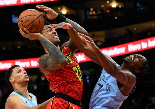 Atlanta Hawks forward John Collins is fouled by Memphis Grizzlies forward Justin Holiday (7) as he shoots during the first quarter of an NBA basketball game, Wednesday, March 13, 2019, in Atlanta. (AP Photo/John Amis)