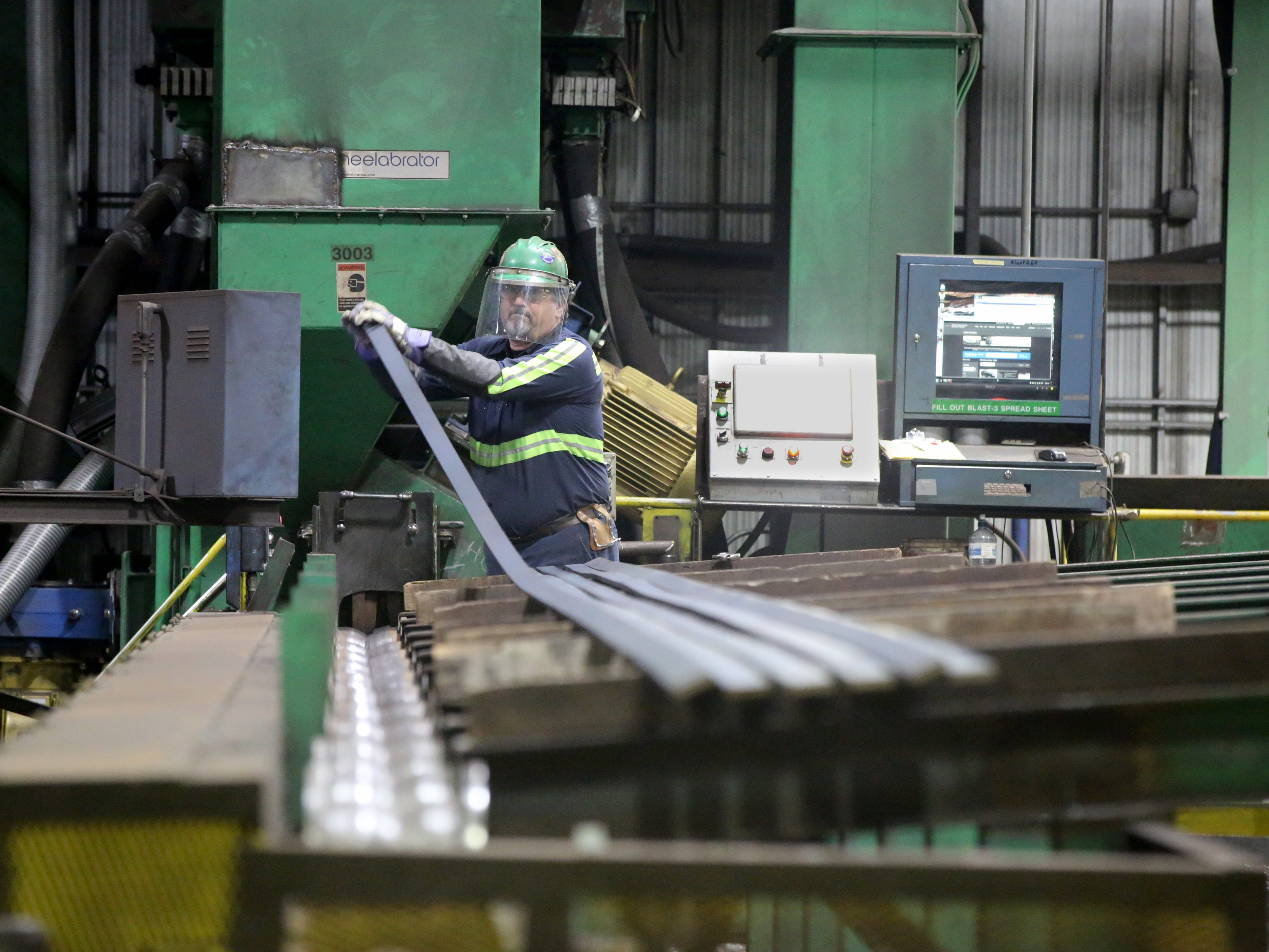 Norm Schultz, a Nucor blaster operator, feeds steel bars to clean for processing.