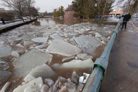 An onlooker takes a photo as City of Fond du Lac public works crews clear an ice jam on the Fond du Lac River that caused flooding Thursday, March 14, 2019, near downtown Fond du Lac.