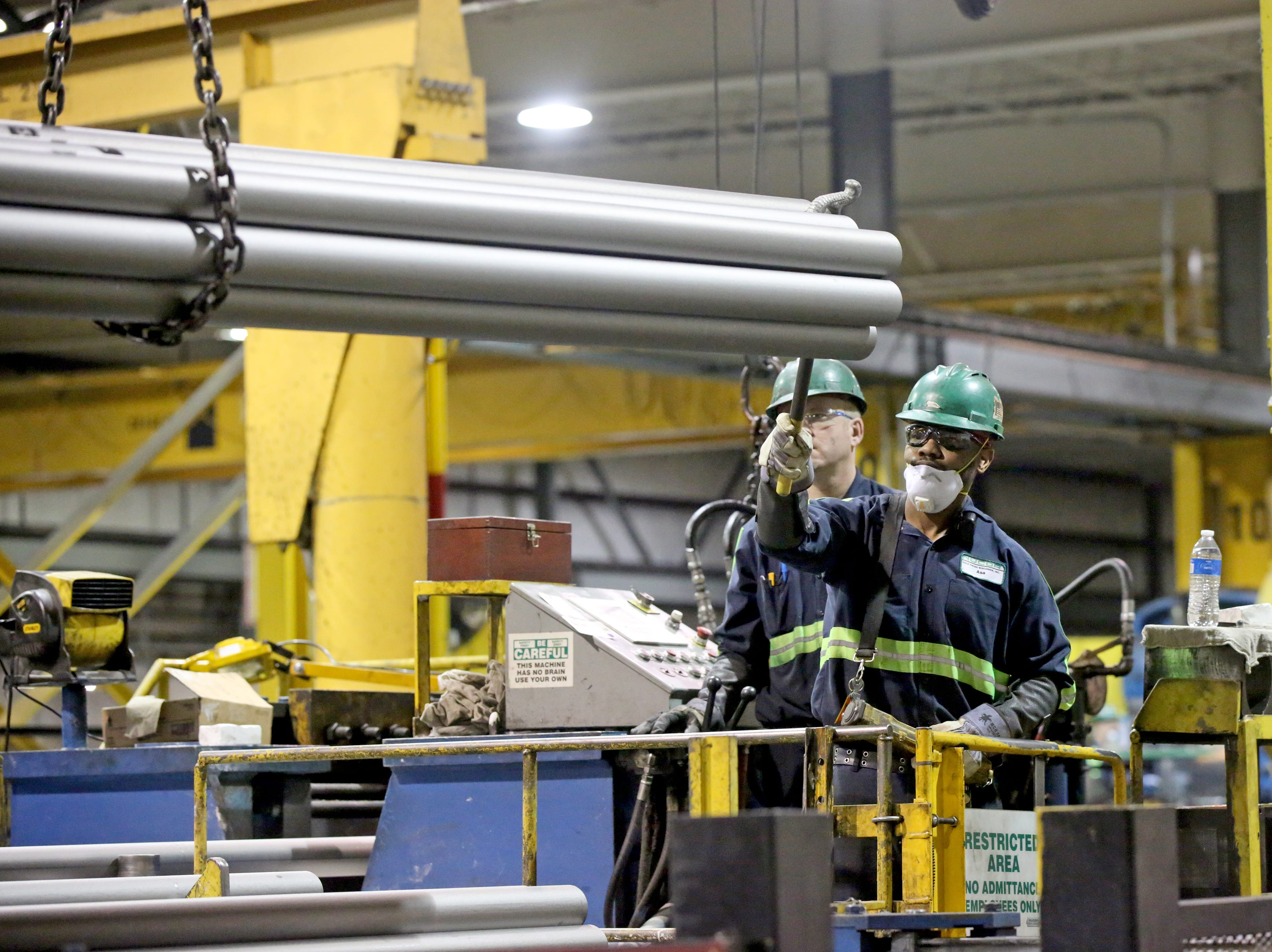 Nucor crane operators Asa Perkins (right) and Don Peplinski move cold finished rods on a draw bench March 14 at Nucor in Oak Creek.