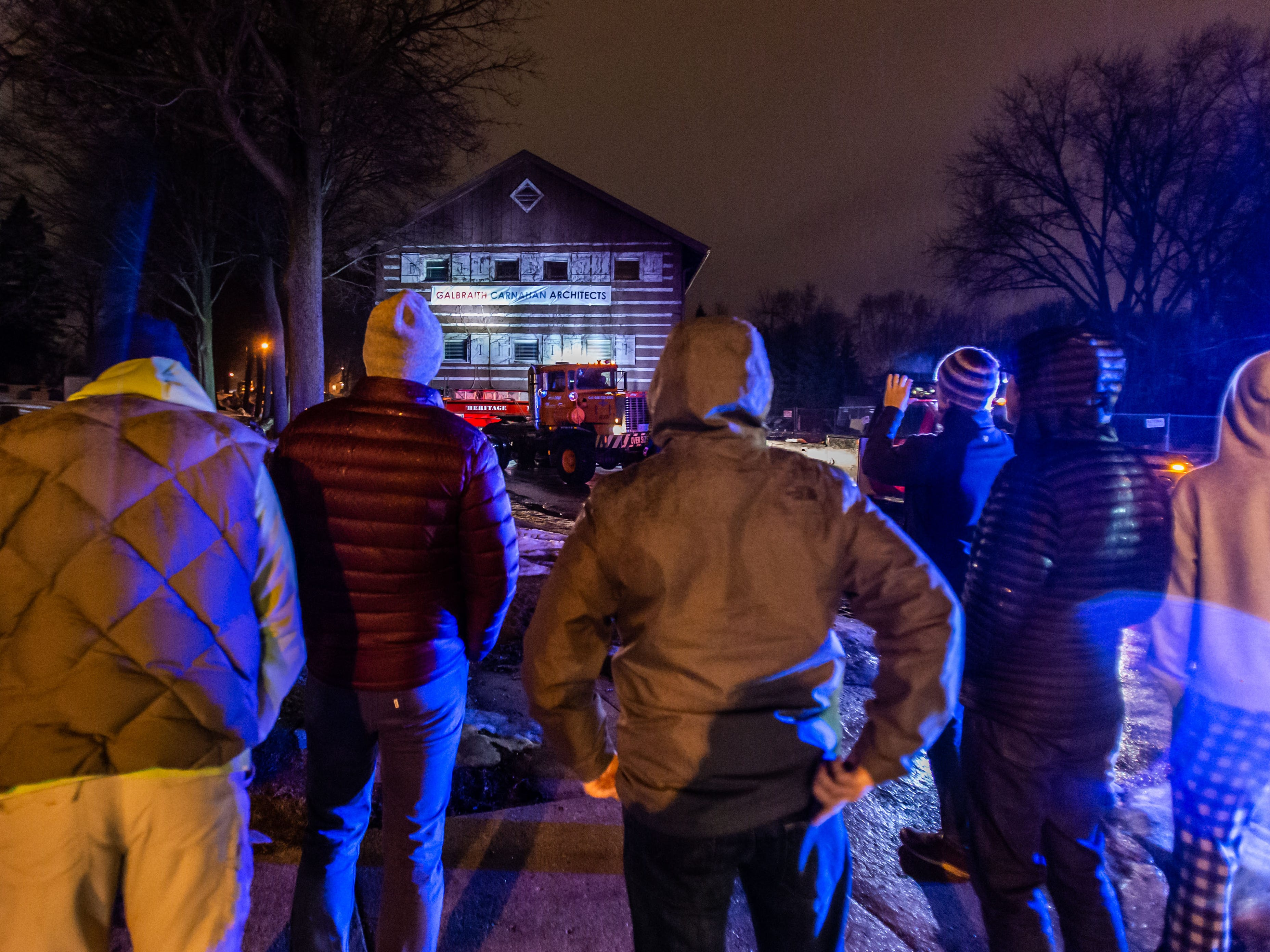 """Spectators look on as Heritage Movers prepare to move the """"Tosa Log Cabin"""" from 2515 N. Wauwatosa Ave. to 6404 W. North Ave. on Wednesday evening, March 13, 2019. The cabin is being moved to make way for a three-story apartment complex called the Gallatin Apartments."""