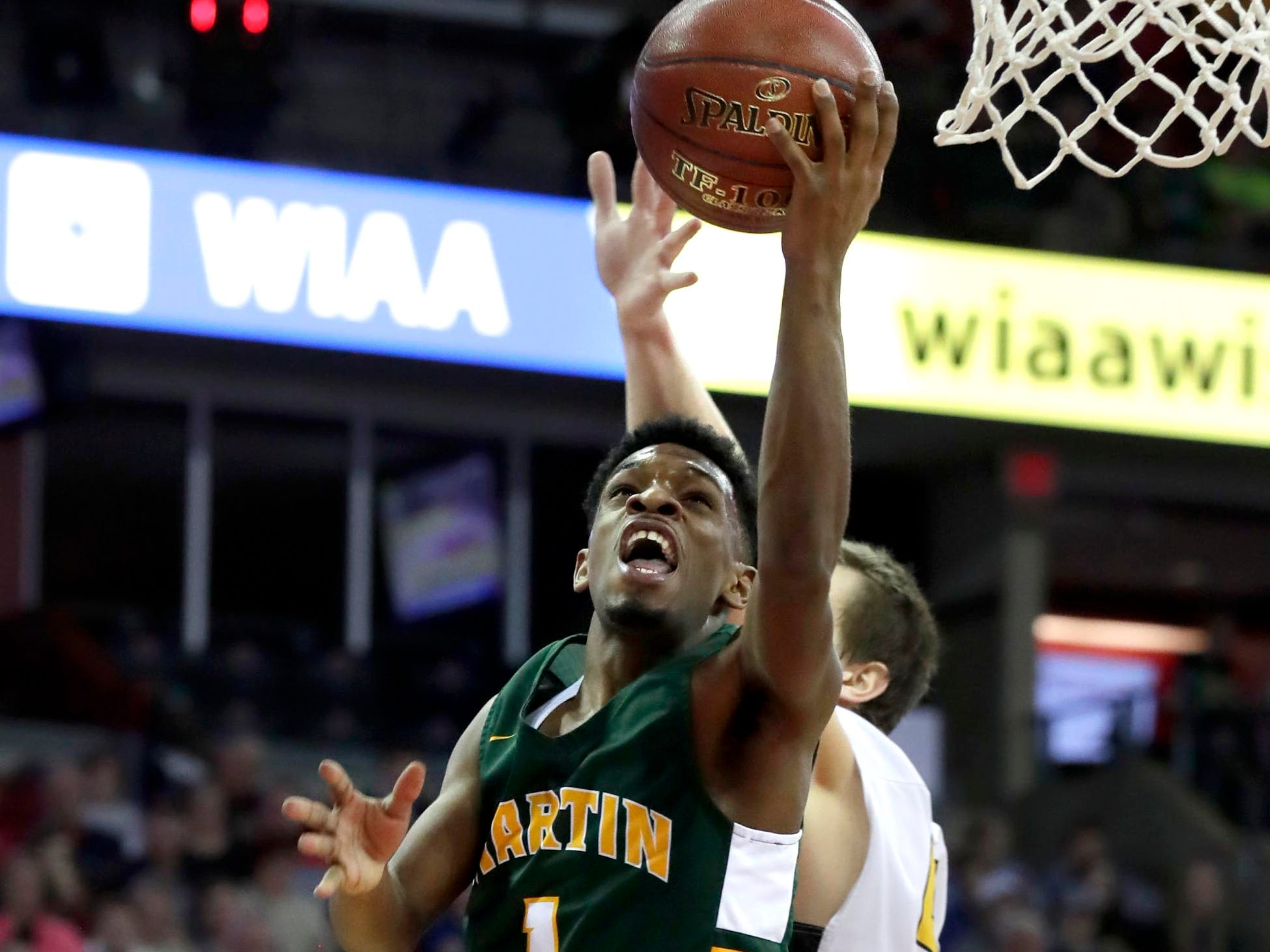 Martin Luther's Trequan Carrington  elevates for two of his 41 points on Thursday.