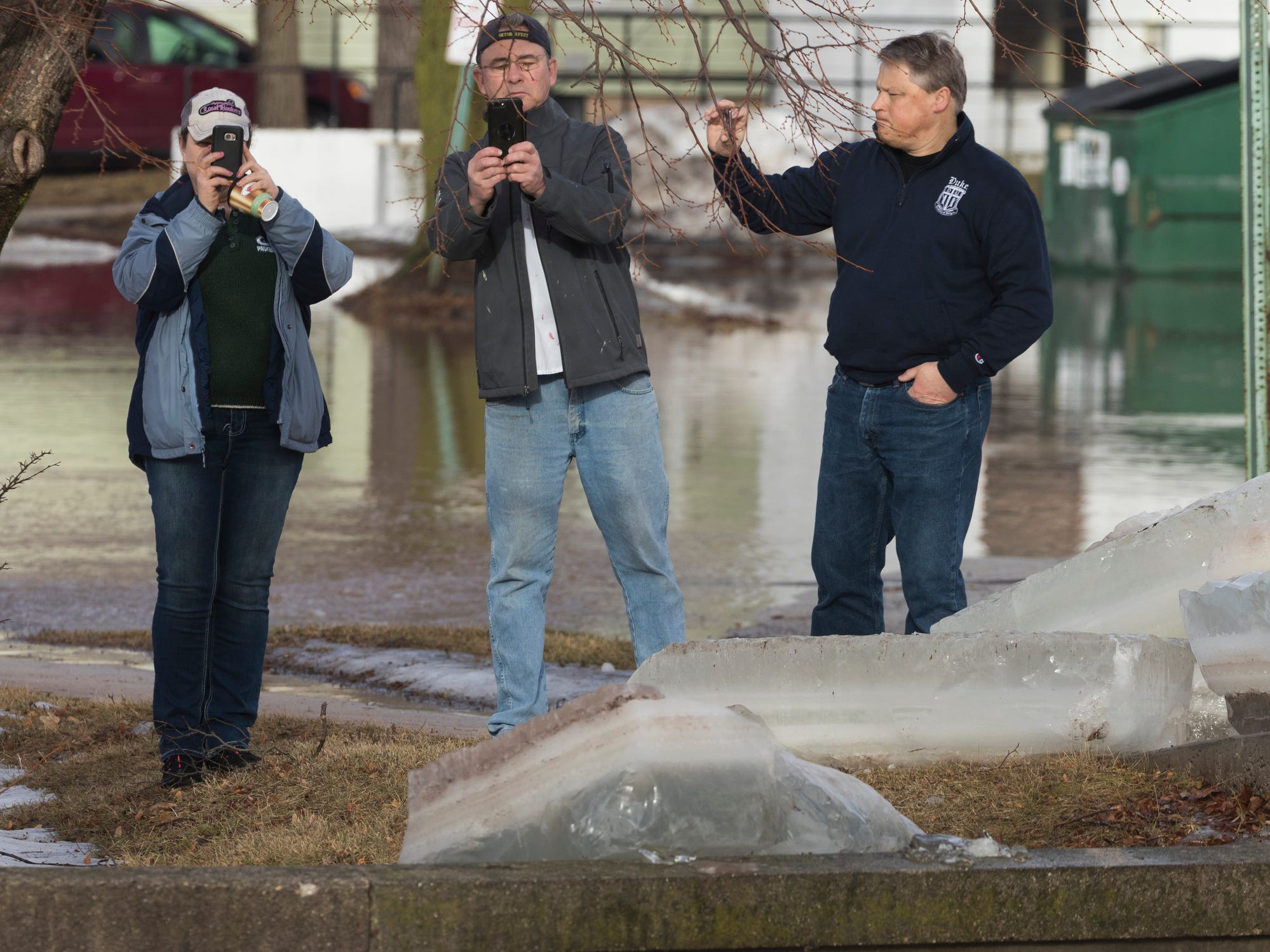 Onlookers take photos as City of Fond du Lac public works crews clear an ice jam on the Fond du Lac River.