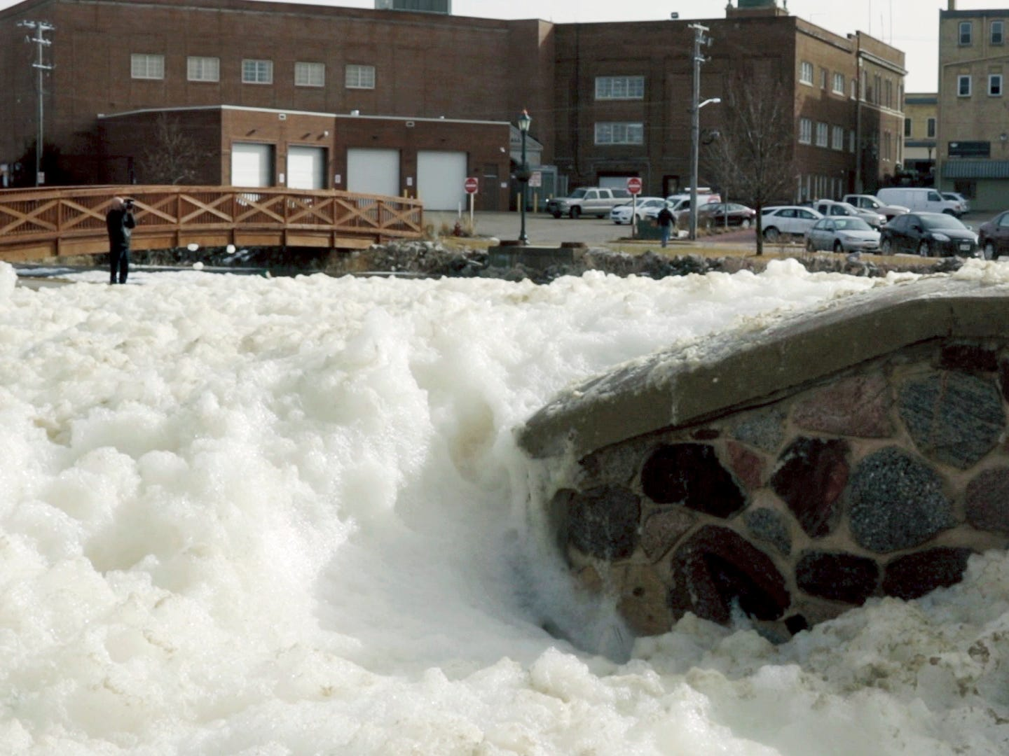 City of Hartford employee Jack Ewing films the foam buildup on the Rubicon River on Thursday, March 14, 2019, in Hartford, Wis. The melting snow, overnight rain and field runoff is what created the large amount of foam to build up.