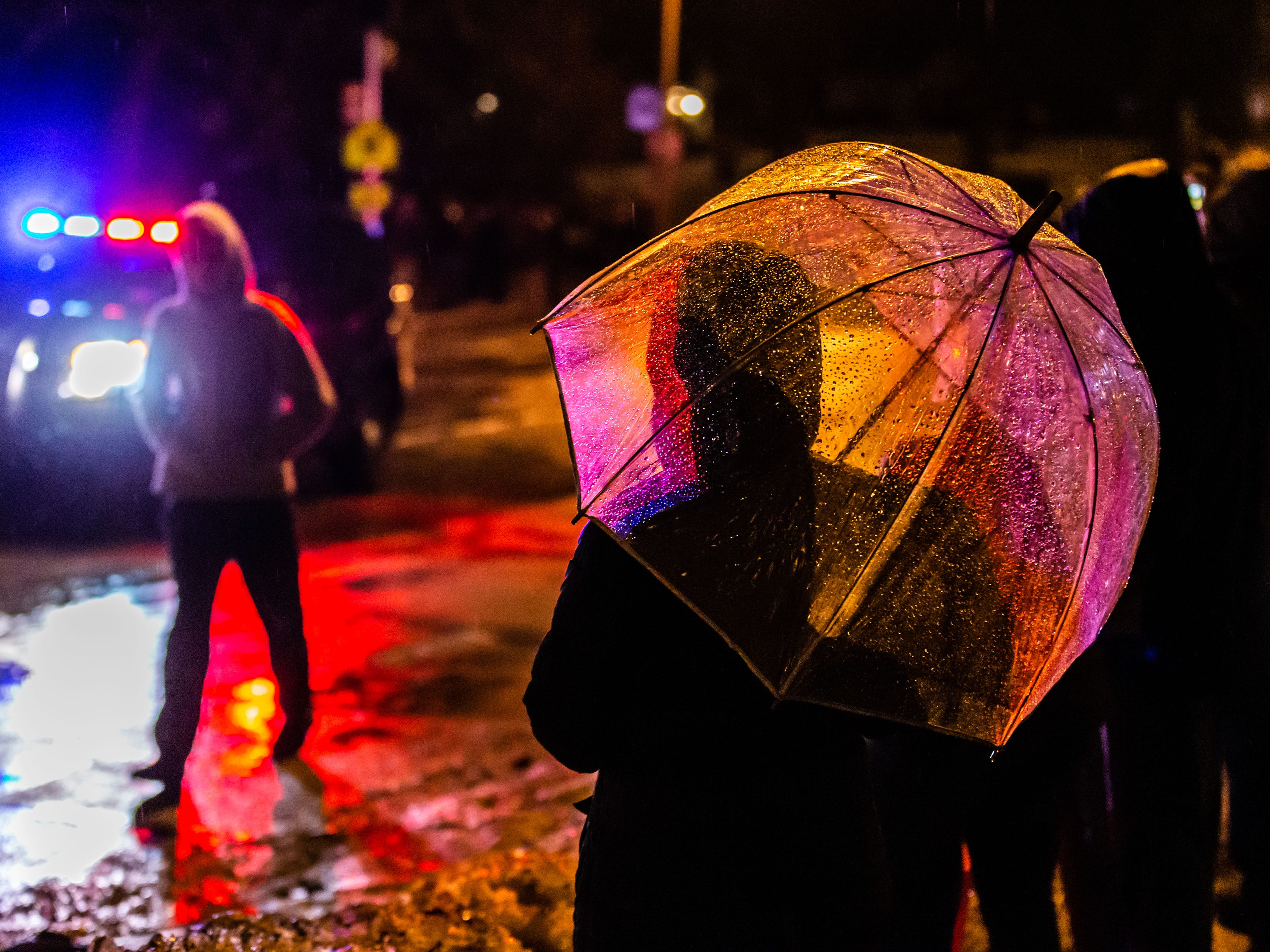 """Spectators look on as the """"Tosa Log Cabin"""" embarks on it's journey from 2515 N. Wauwatosa Ave. to 6404 W. North Ave. on Wednesday evening, March 13, 2019. The cabin is being moved to make way for a three-story apartment complex called the Gallatin Apartments."""