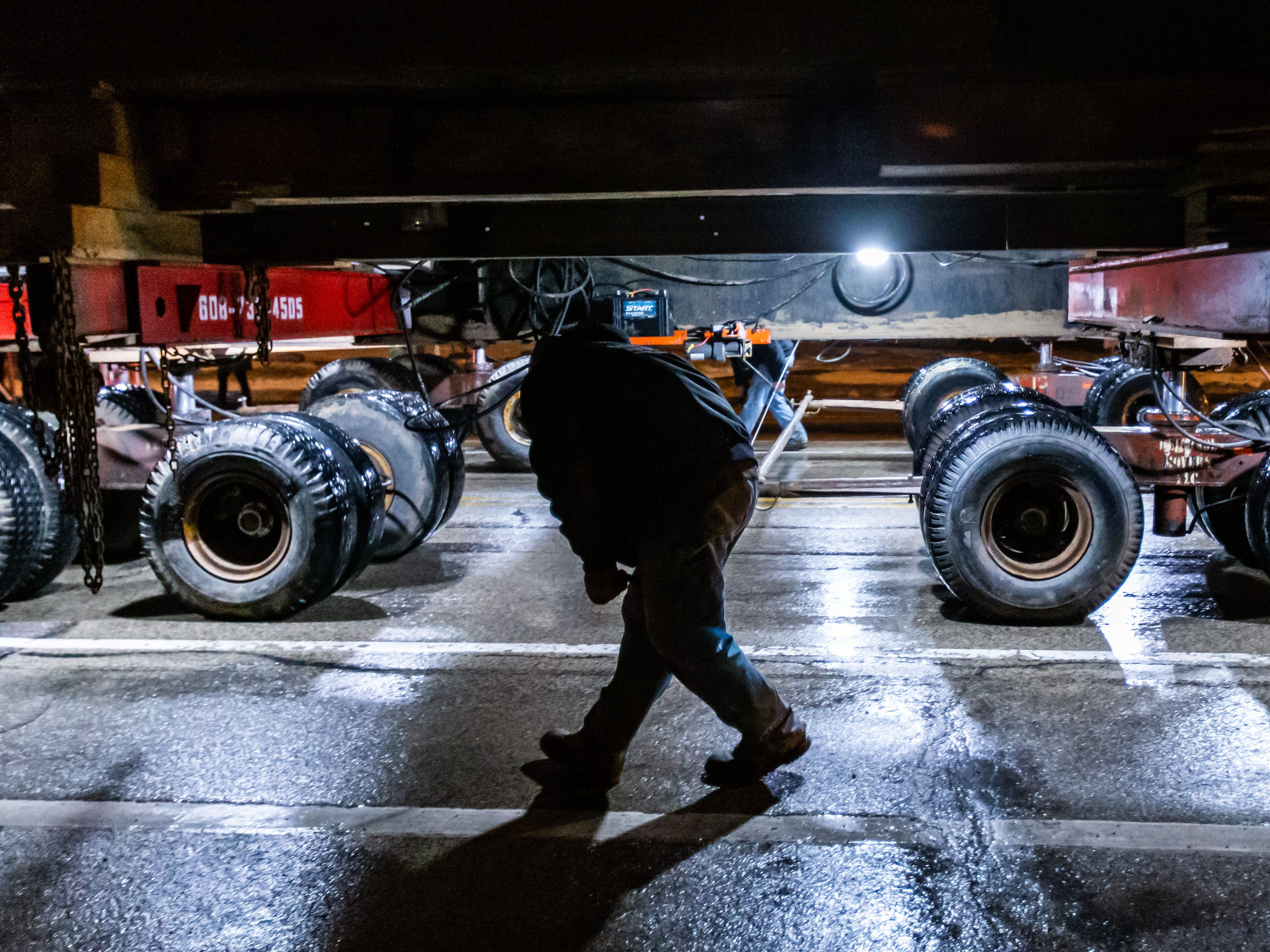 """Employees from Heritage Movers keep a close watch on the """"Tosa Log Cabin"""" as it rolls down N. Wauwatosa Ave. on it's journey to 6404 W. North Ave. on Wednesday evening, March 13, 2019. The cabin is being moved to make way for a three-story apartment complex called the Gallatin Apartments."""