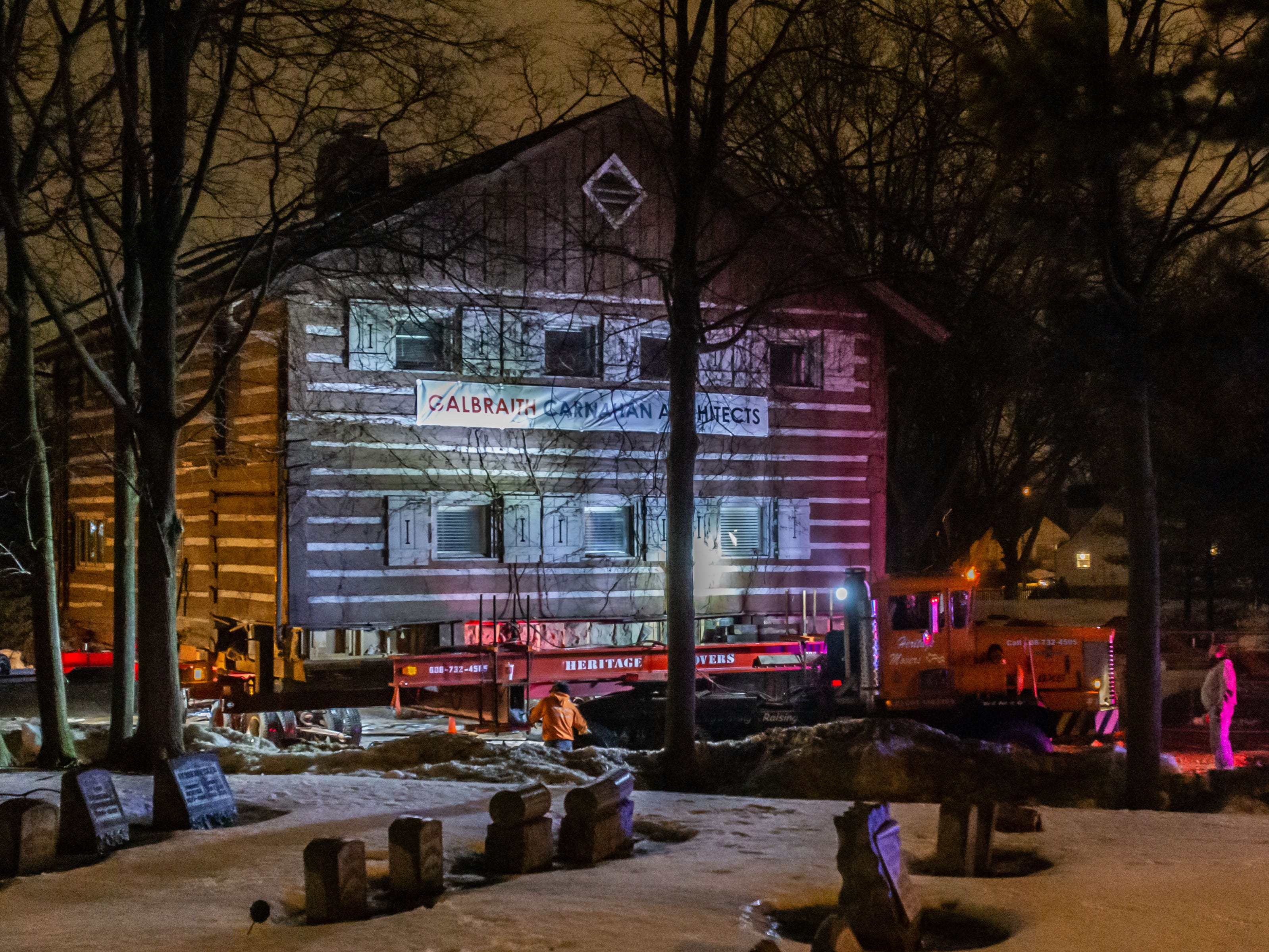 """A crew from Heritage Movers prepare to move the """"Tosa Log Cabin"""" from 2515 N. Wauwatosa Ave. to 6404 W. North Ave. on Wednesday evening, March 13, 2019. The cabin is being moved to make way for a three-story apartment complex called the Gallatin Apartments."""