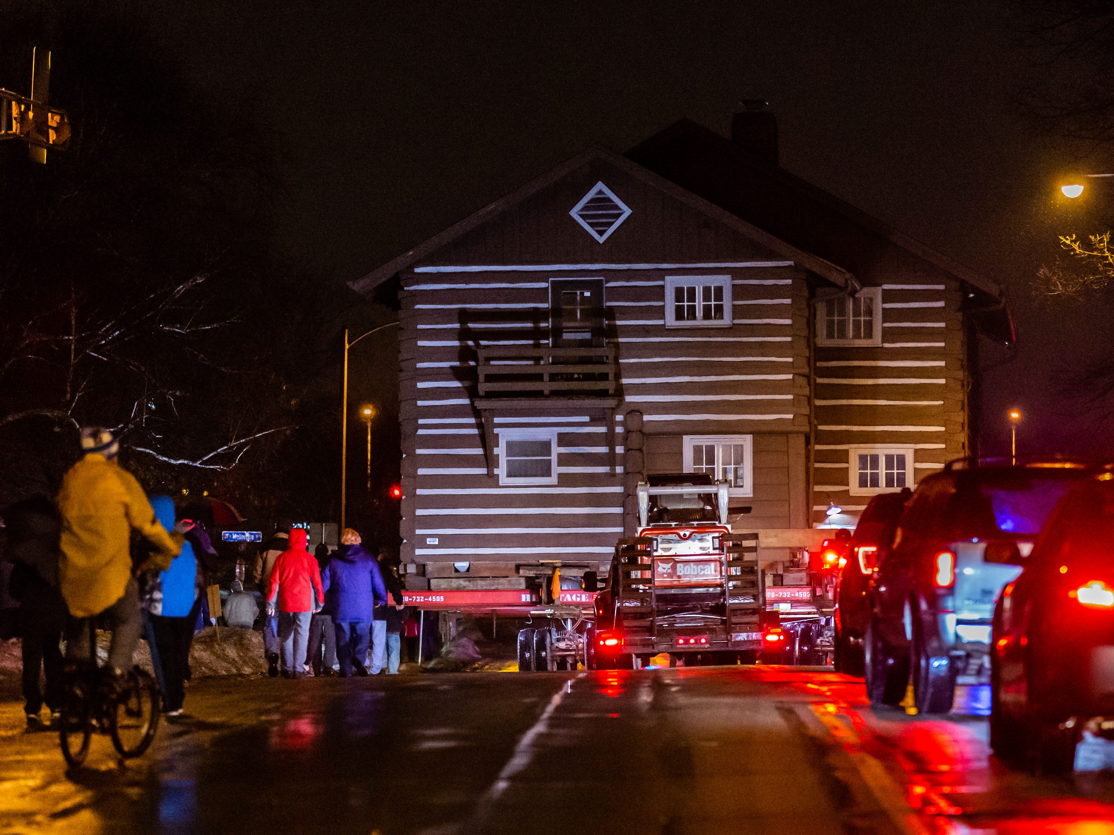 """Spectators follow along as the """"Tosa Log Cabin"""" rolls down N. Wauwatosa Ave. to it's destination at 6404 W. North Ave. on Wednesday evening, March 13, 2019. The cabin is being moved to make way for a three-story apartment complex called the Gallatin Apartments."""