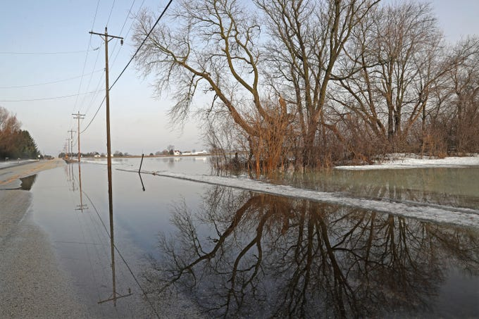 Shallow water edges out over part of Petersen Road near the intersection with West Shore Drive in the Town of Merton Thursday. Melting snow and rain on top of frozen farm fields is causing causing spring flooding in western Waukesha County.