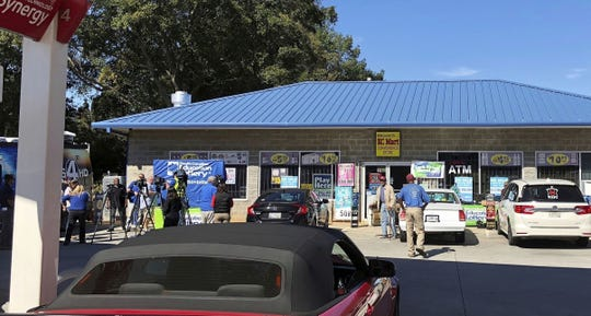 In this Oct. 24, 2018, file photo, media, at left, record people entering the KC Mart in Simpsonville, S.C., after it was announced the winning Mega Millions lottery ticket was purchased at the store. The South Carolina lottery says a single winner has stepped forward to claim the $1.5 billion Jackpot from a drawing last October.