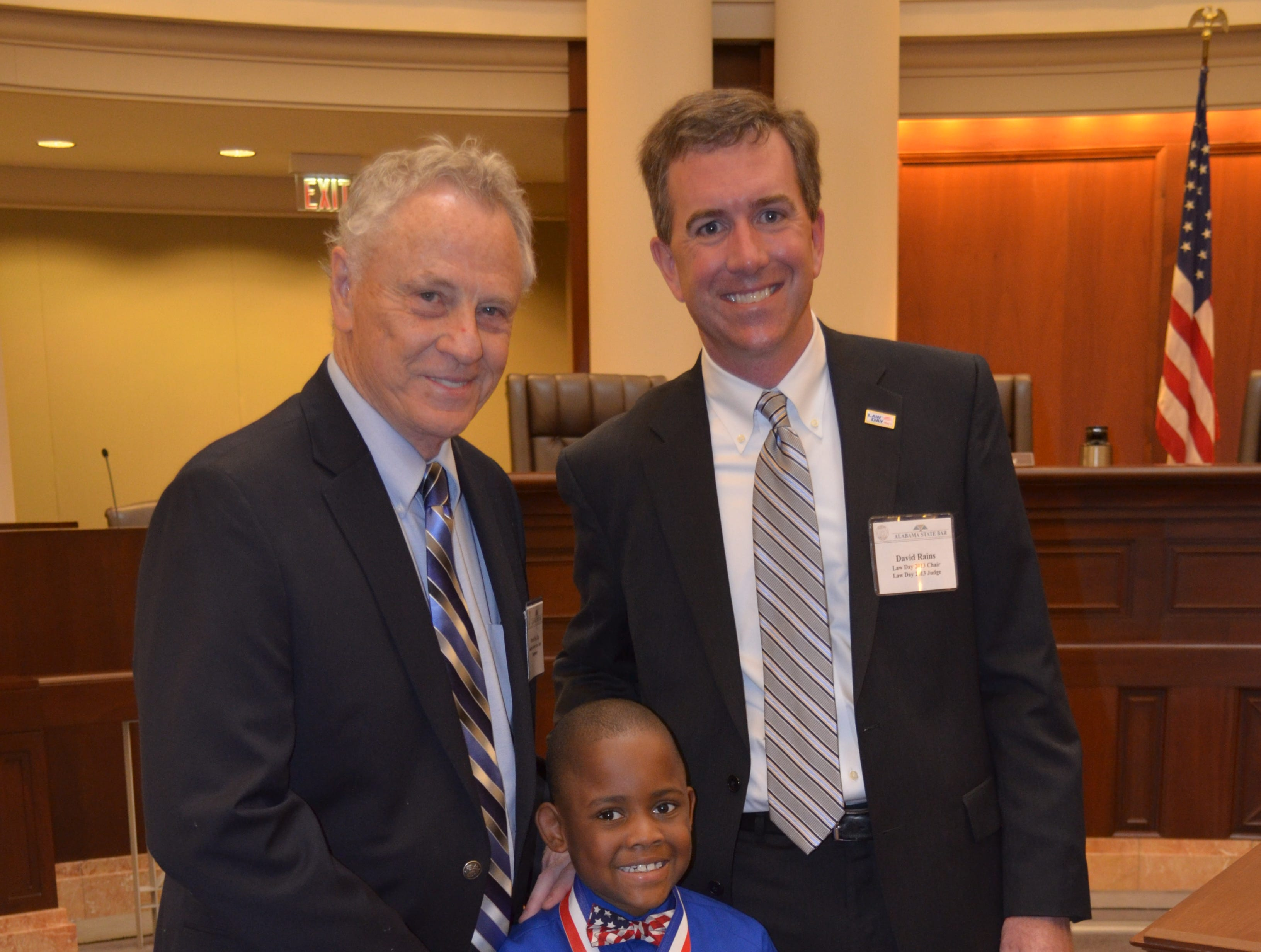 Morris Dees, left, and David Rains present a poster award to Jelan Smith. Alvin Benn/Special to the Advertiser Morris Dees, left and David Rains present a poster award to Jelan (cq) Smith of Mixon Elementary School in Ozark at Wednesday's Law Day program. . 5-1-13
