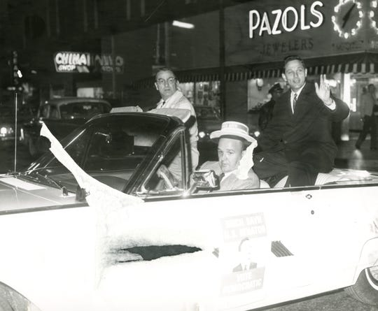 The Pazols sign is visible behind Birch Bayh during a 1962 parade along Walnut Street in downtown Muncie.
