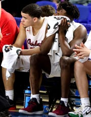 Oakland senior Lamarius Jackson, left, and junior Mandrell Grant watch the final seconds of the game from the bench Thursday.
