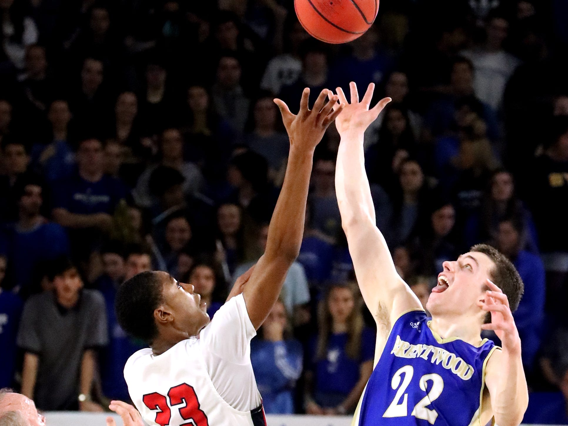 Oakland's Dorian Anderson (23) and Brentwood's Harry Lackey (22) jump the ball to start the overtime period of the quarterfinal round of the TSSAA Class AAA Boys State Tournament, on Thursday, March 14, 2019, at Murphy Center in Murfreesboro, Tenn.