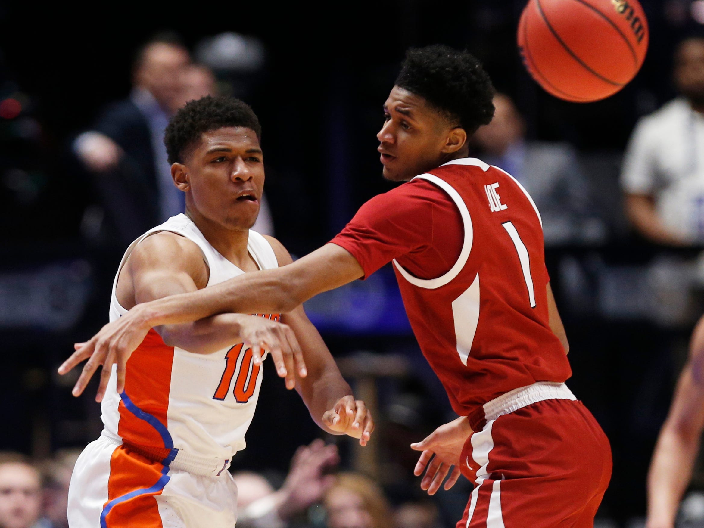 Florida guard Noah Locke (10) passes the ball around Arkansas guard Isaiah Joe (1) during the first half of the SEC Men's Basketball Tournament game at Bridgestone Arena in Nashville, Tenn., Thursday, March 14, 2019.