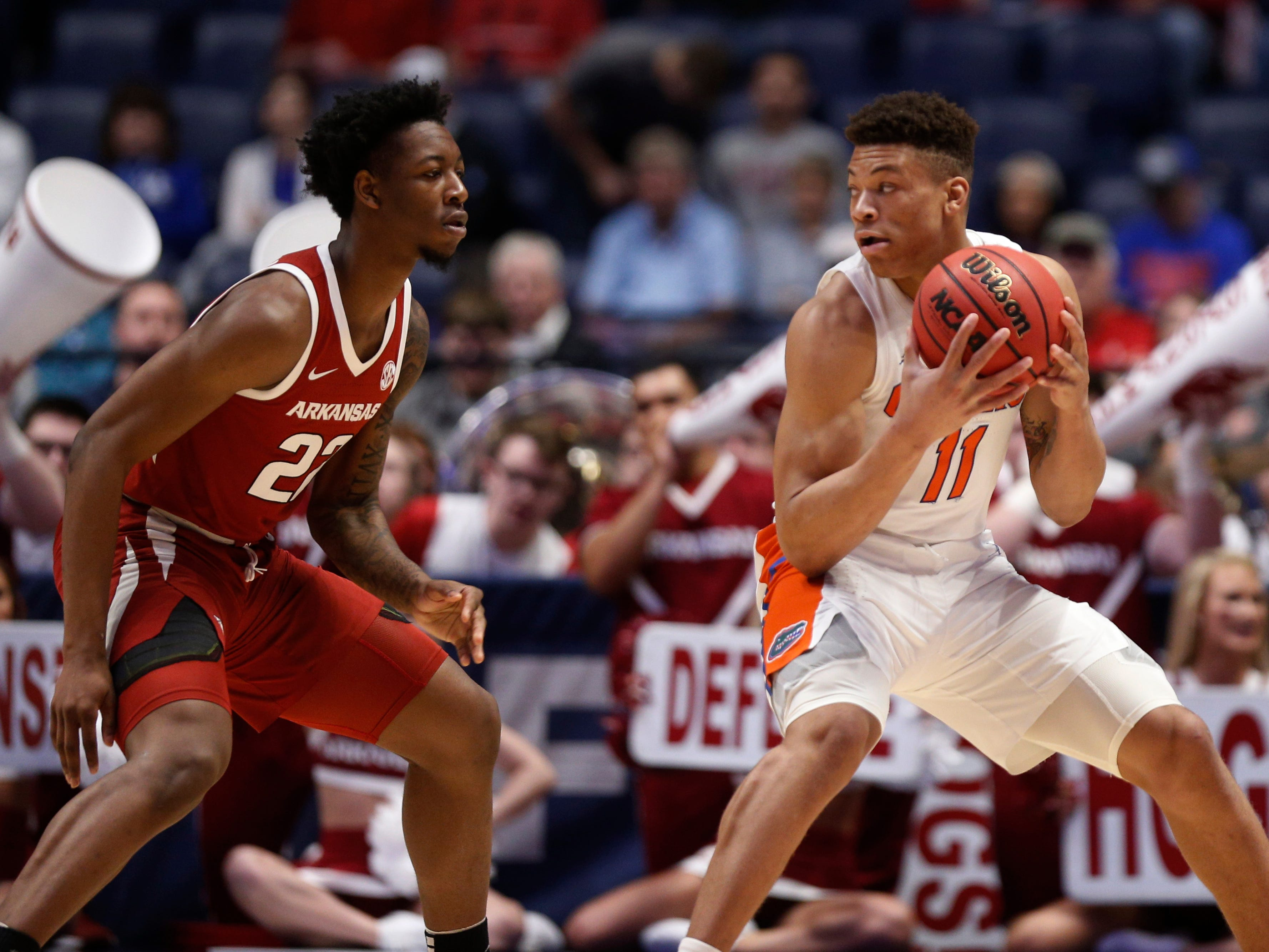 Florida forward Keyontae Johnson (11) tries to move the ball defended by Arkansas forward Gabe Osabuohien (22) during the first half of the SEC Men's Basketball Tournament game at Bridgestone Arena in Nashville, Tenn., Thursday, March 14, 2019.