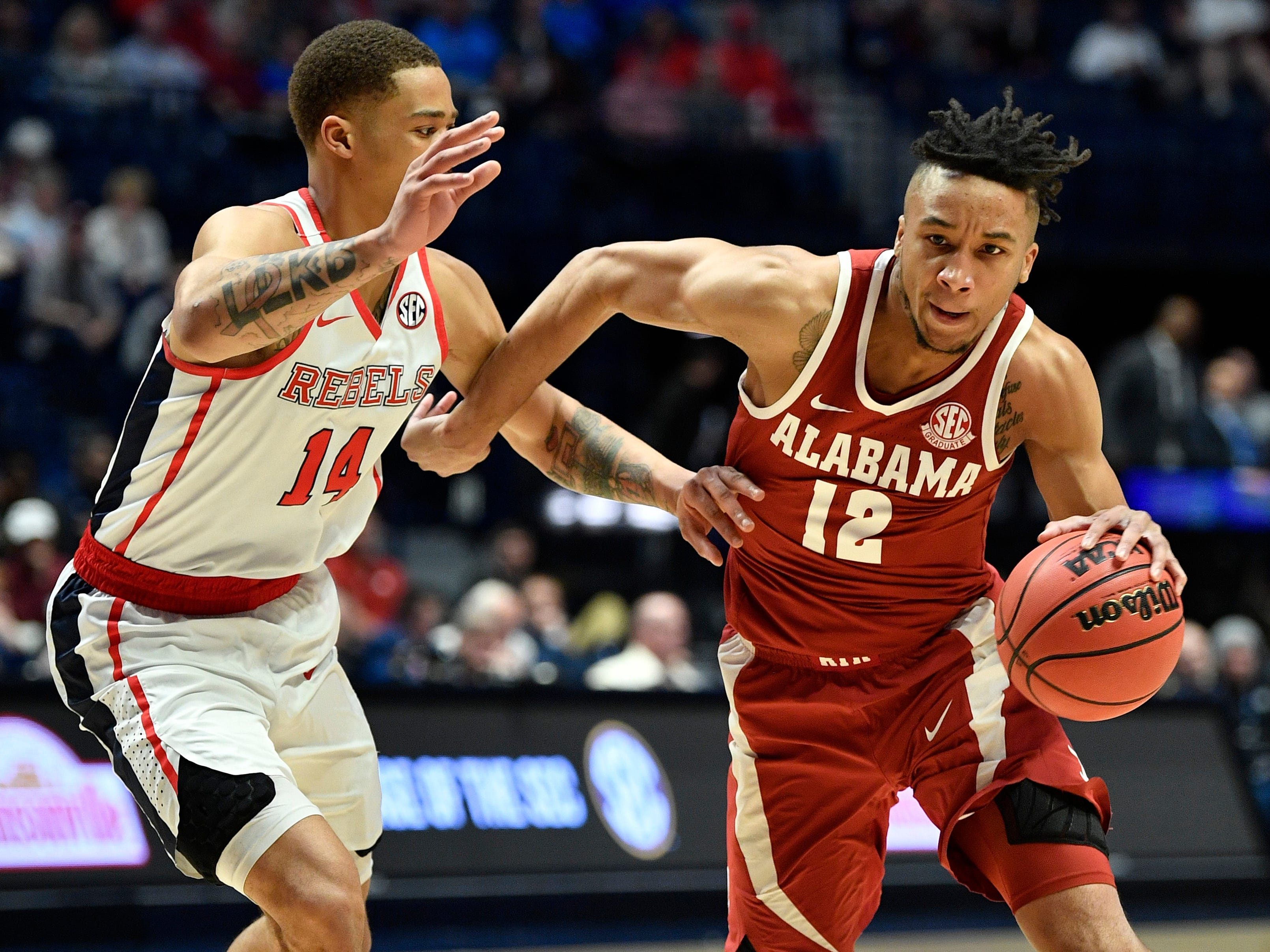 Alabama guard Dazon Ingram (12) moves the ball defended by Ole Miss forward KJ Buffen (14) during the first half of the SEC Men's Basketball Tournament game at Bridgestone Arena in Nashville, Tenn., Thursday, March 14, 2019.