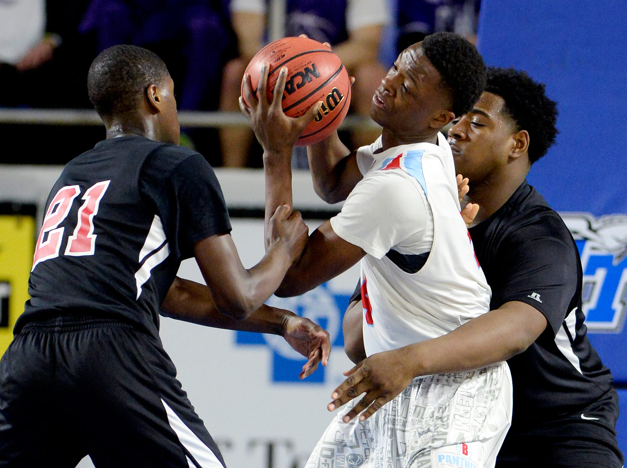 Brainerd forward Laderron Freeman, center, is pressured by Pearl-Cohn guard Antonio Anthony (21) forward Wiiliam Griffin (52) during the second half of an Class AA boys' state basketball quarterfinal game against Brainerd Wednesday, March 13, 2019, in Murfreesboro, Tenn. Brainerd won 76-73.